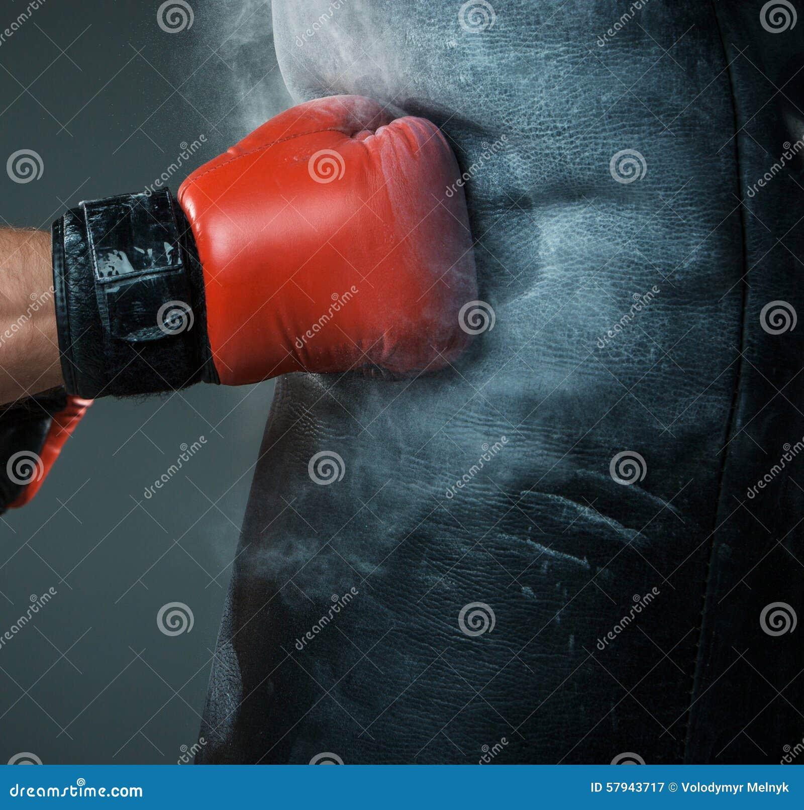 Mano del boxeador y del saco de arena sobre negro