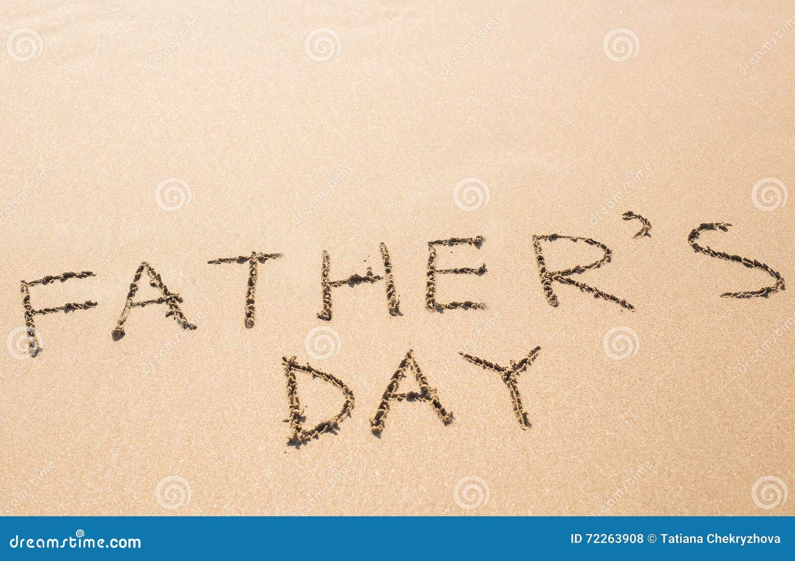 Mano del día de padre escrita en la playa arenosa