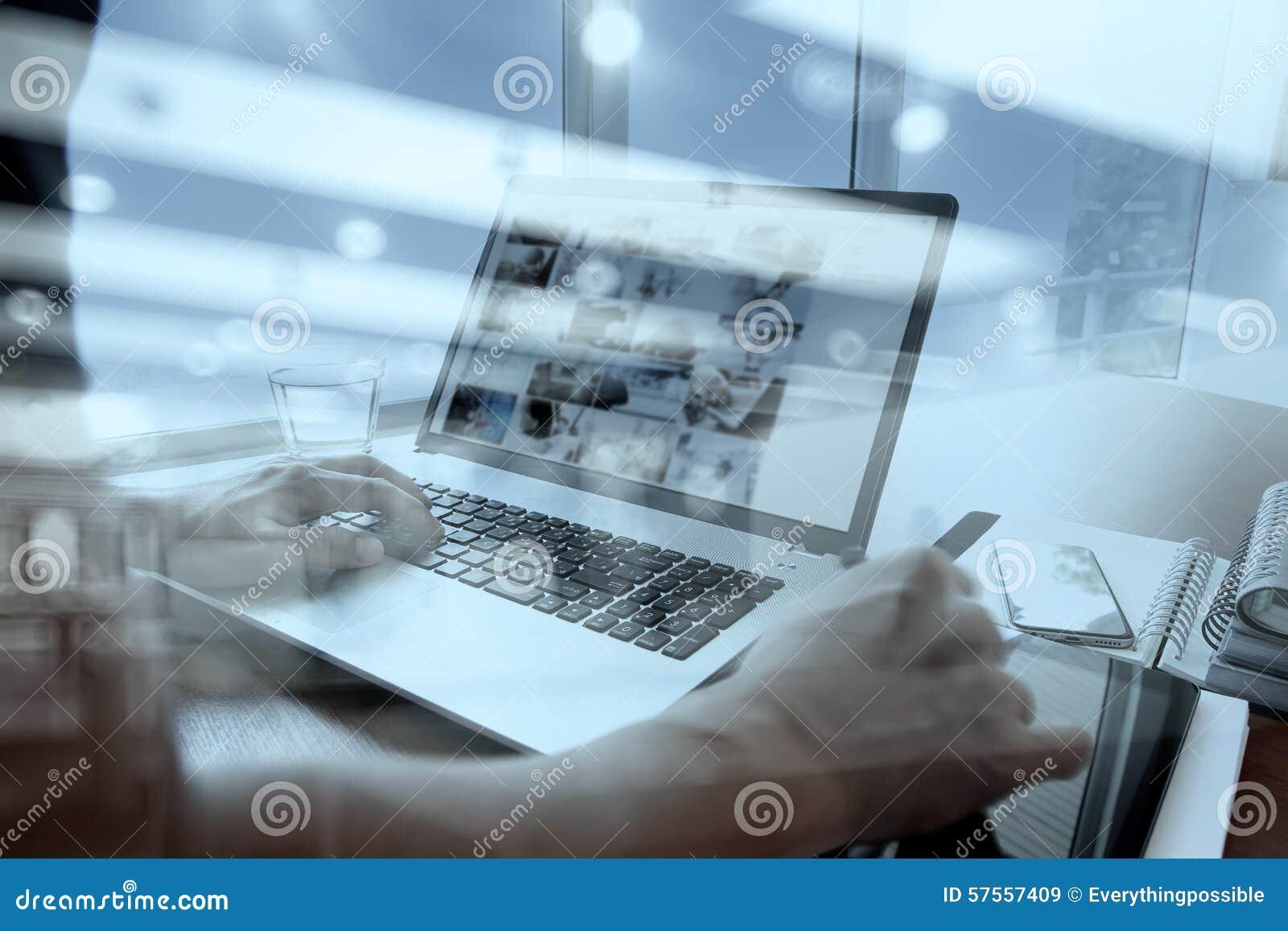 Mano del diseñador que trabaja con la tableta y el ordenador portátil digitales