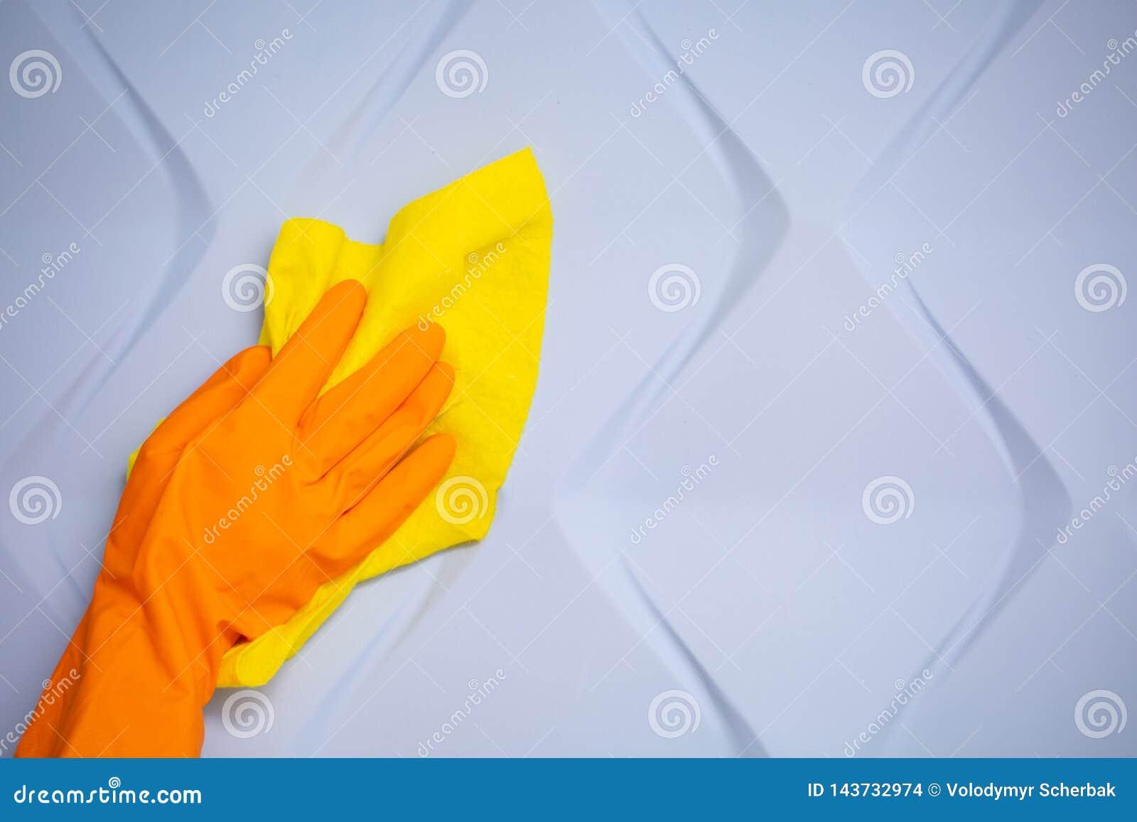 Mano del empleado en el guante protector de goma anaranjado que limpia la pared azul 3d del polvo con el trapo seco amarillo Limp