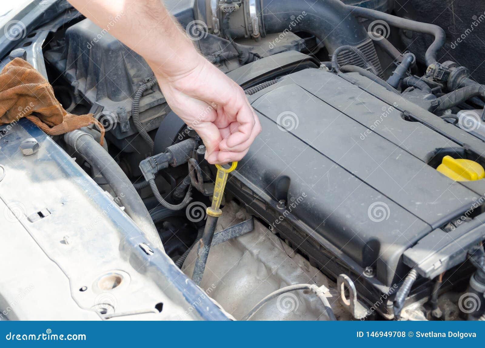 Mano del meccanico con uno strumento sotto il cappuccio dell automobile