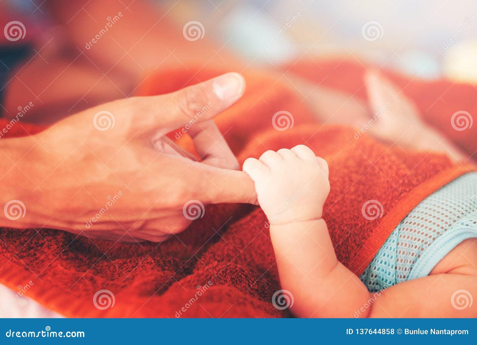 Mano del neonato della tenuta del padre Concetto  nucleo familiare  felice Bella immagine concettuale di maternità, mano del raga