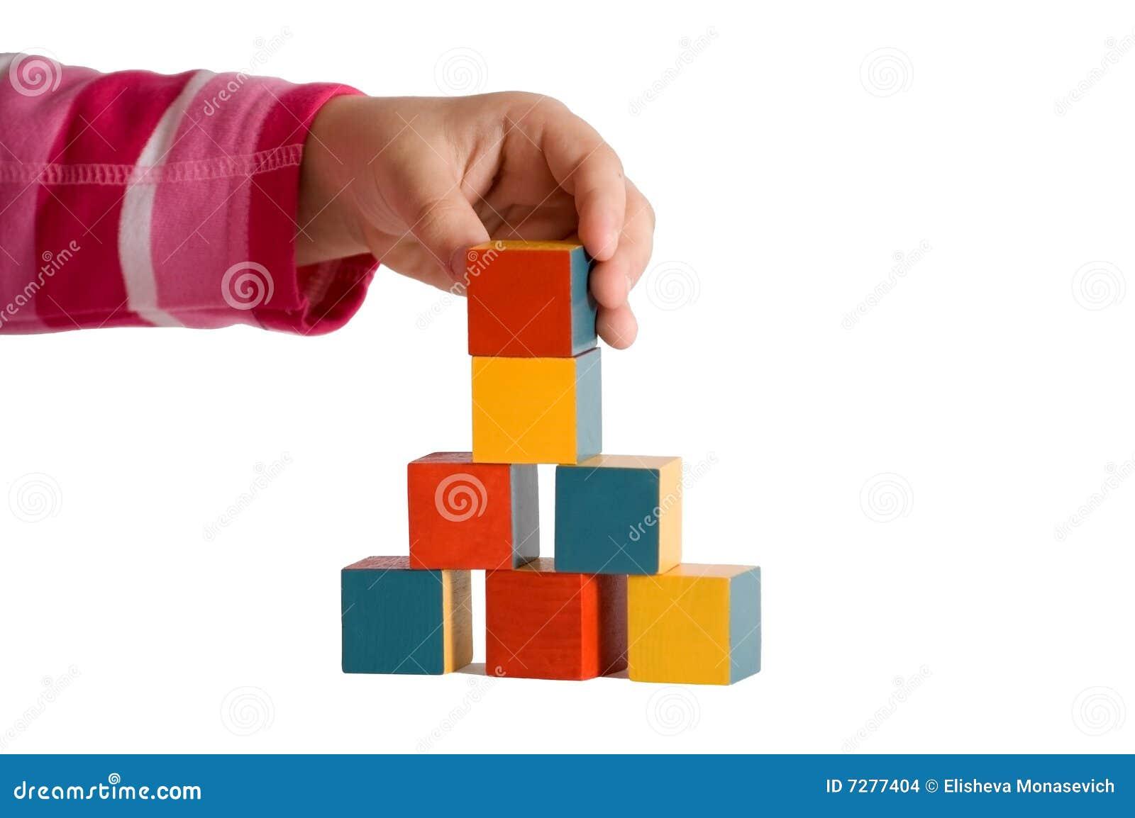Mano del niño que construye una torre