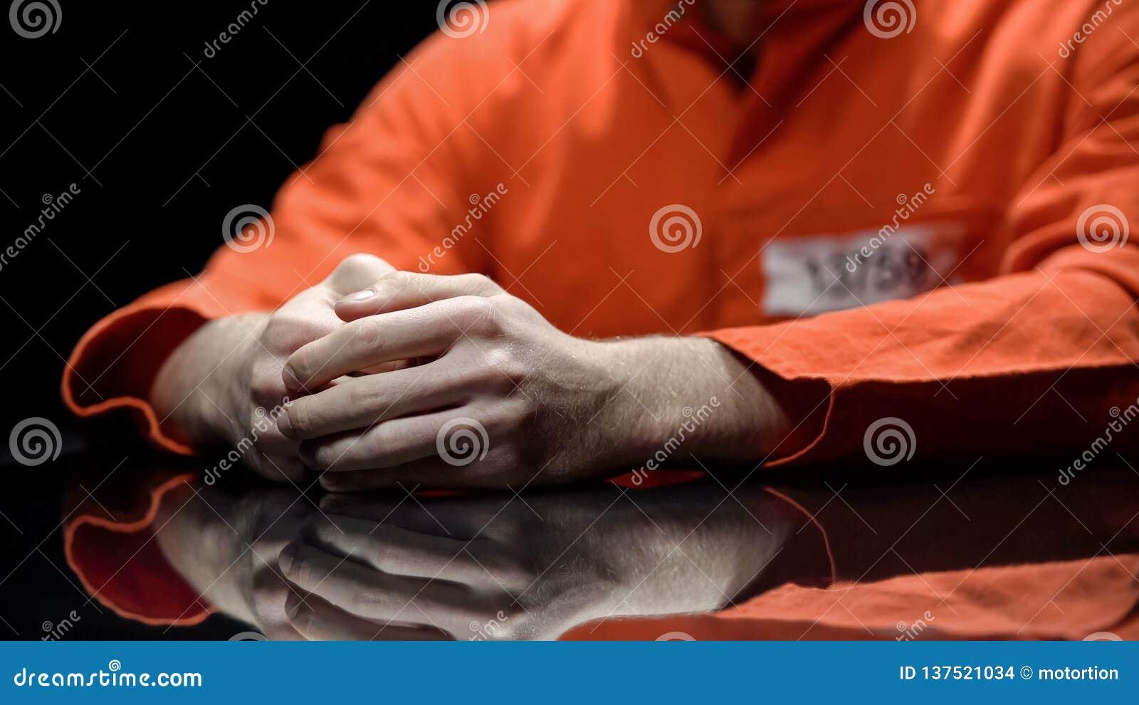 Mano del preso masculino, interno que da pruebas en el sitio de detención, cooperación