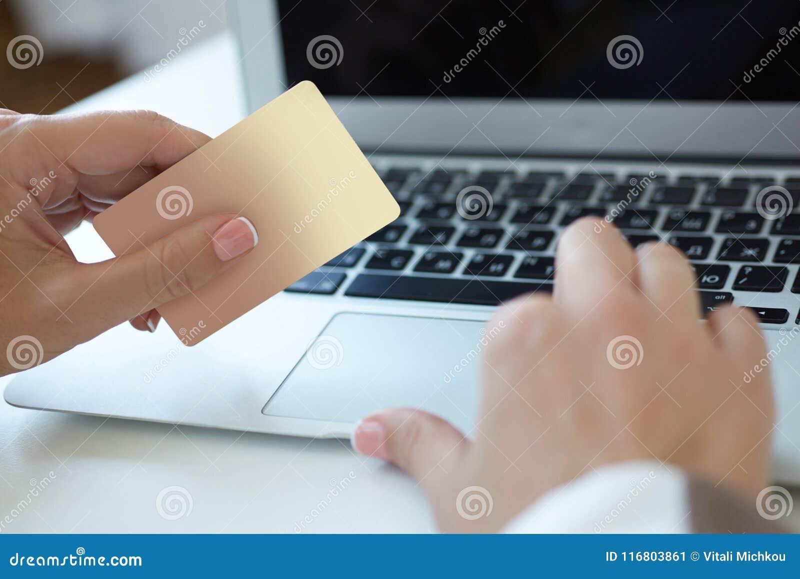 Mano del primo piano dei dettagli di battitura a macchina della carta di credito della ragazza sul computer portatile al processo