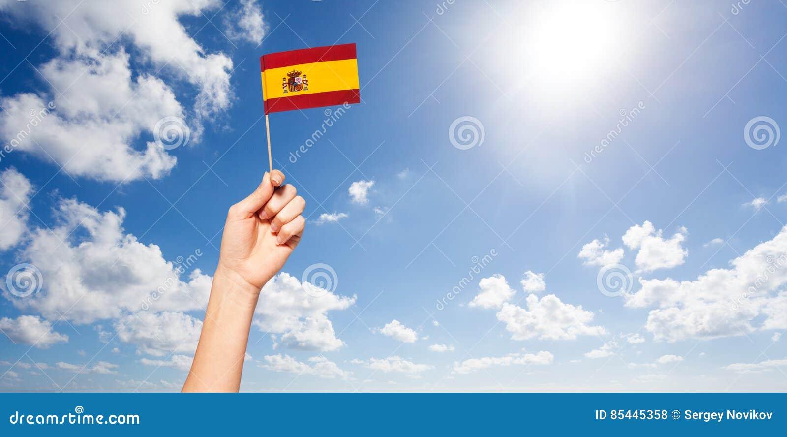 Mano del ` s de la mujer que sostiene la bandera española contra el cielo azul