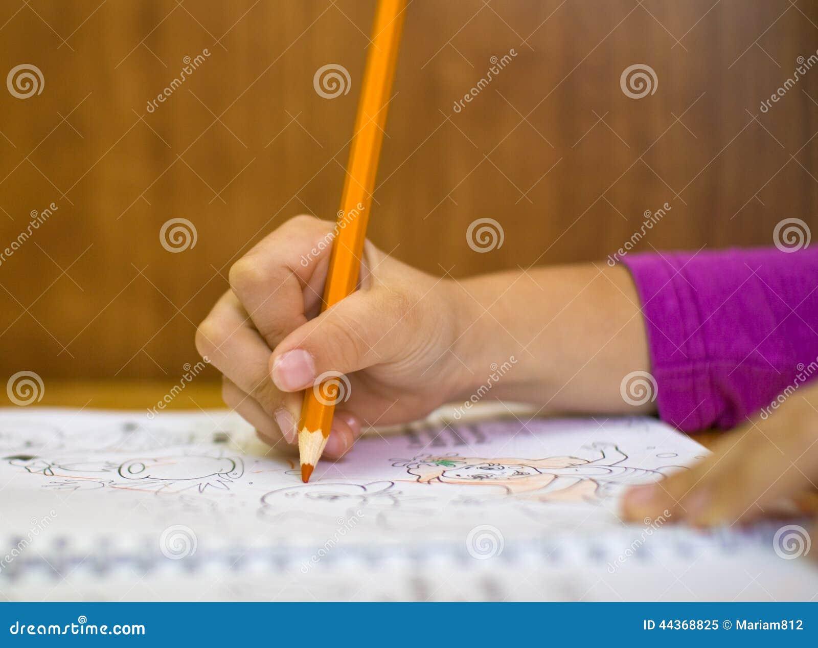 Mano del ` s del bambino con il pensil arancio che assorbe album