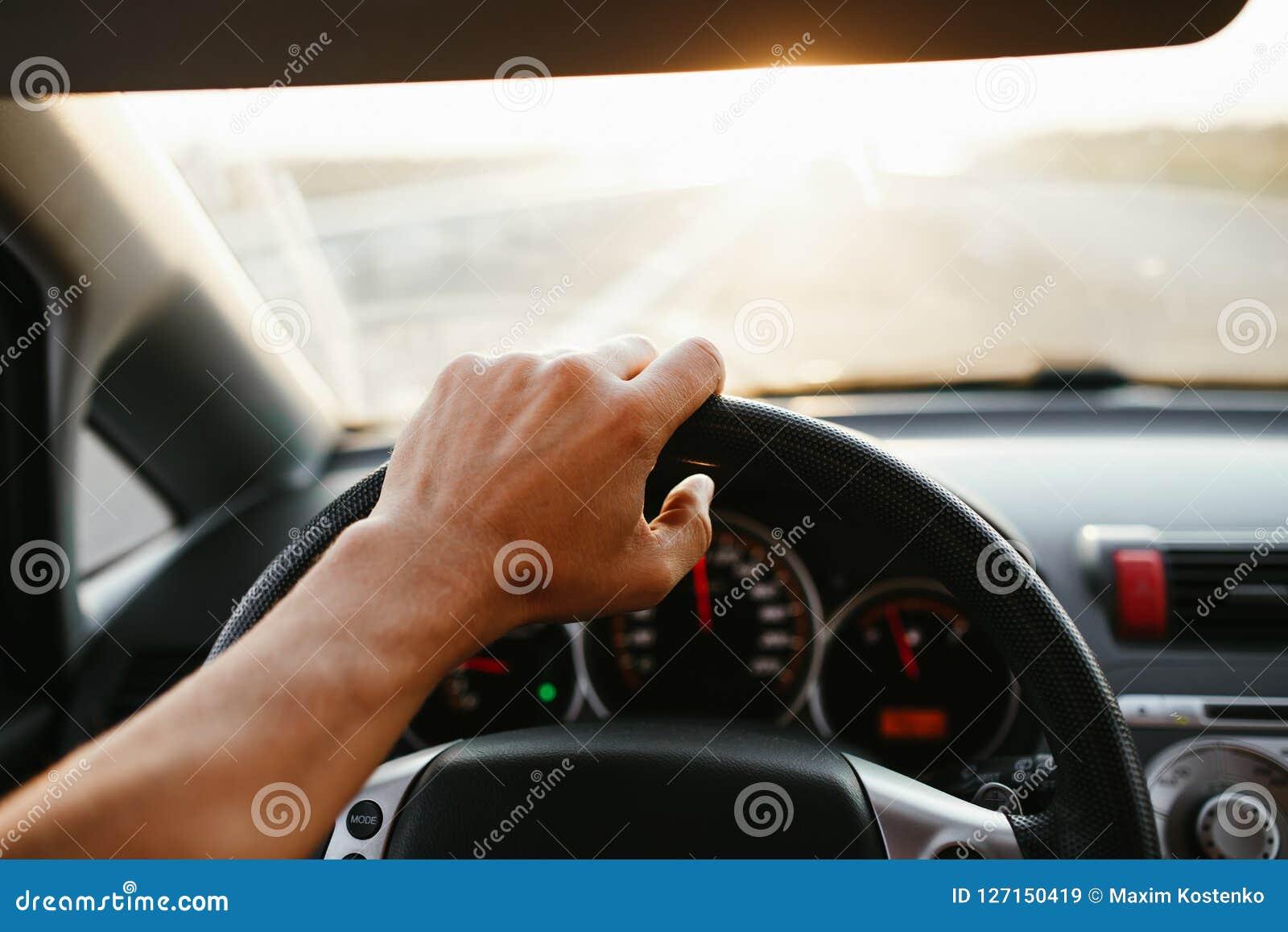 Mano del ` s dell uomo del fuoco selettivo sul volante, conducente un automobile al tramonto Priorità bassa di corsa