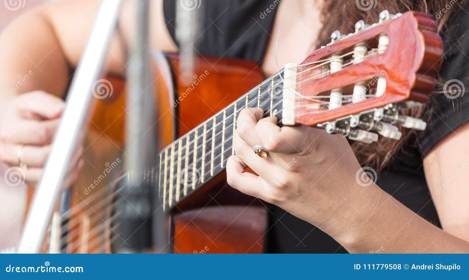 Mano del ` s della ragazza che gioca chitarra