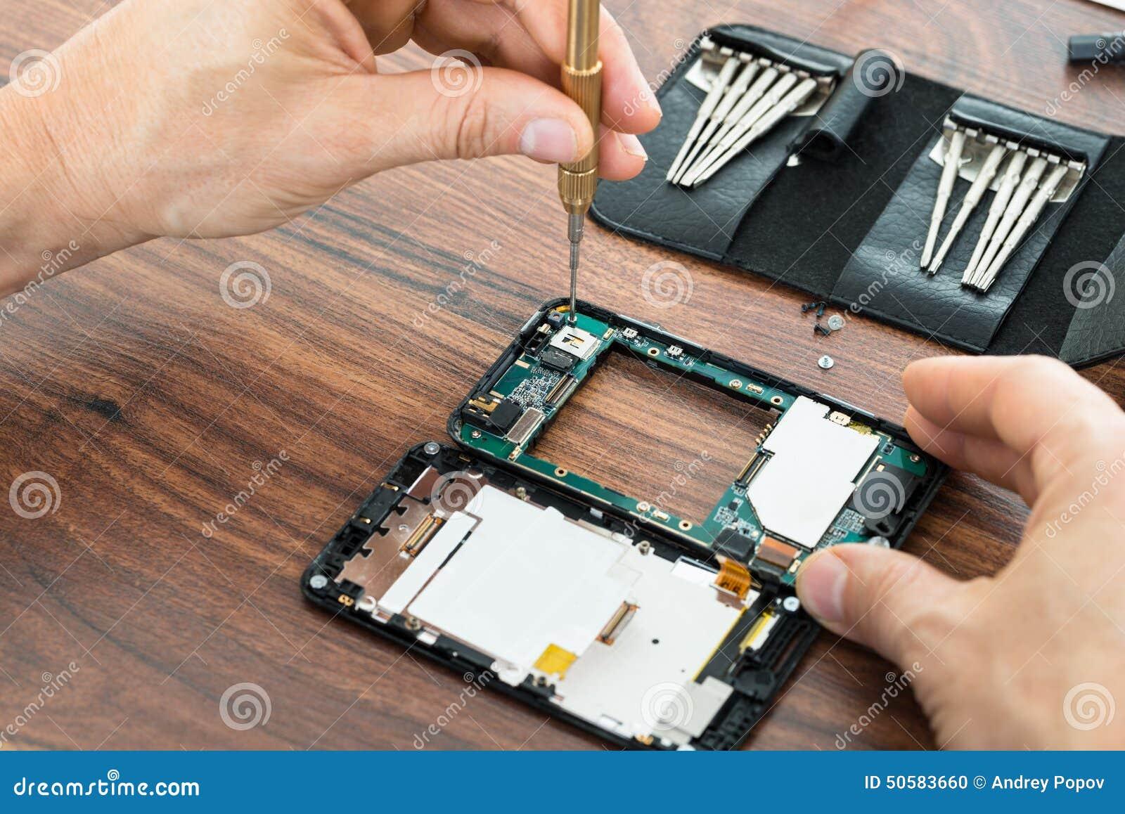 Mano del técnico que repara el teléfono móvil
