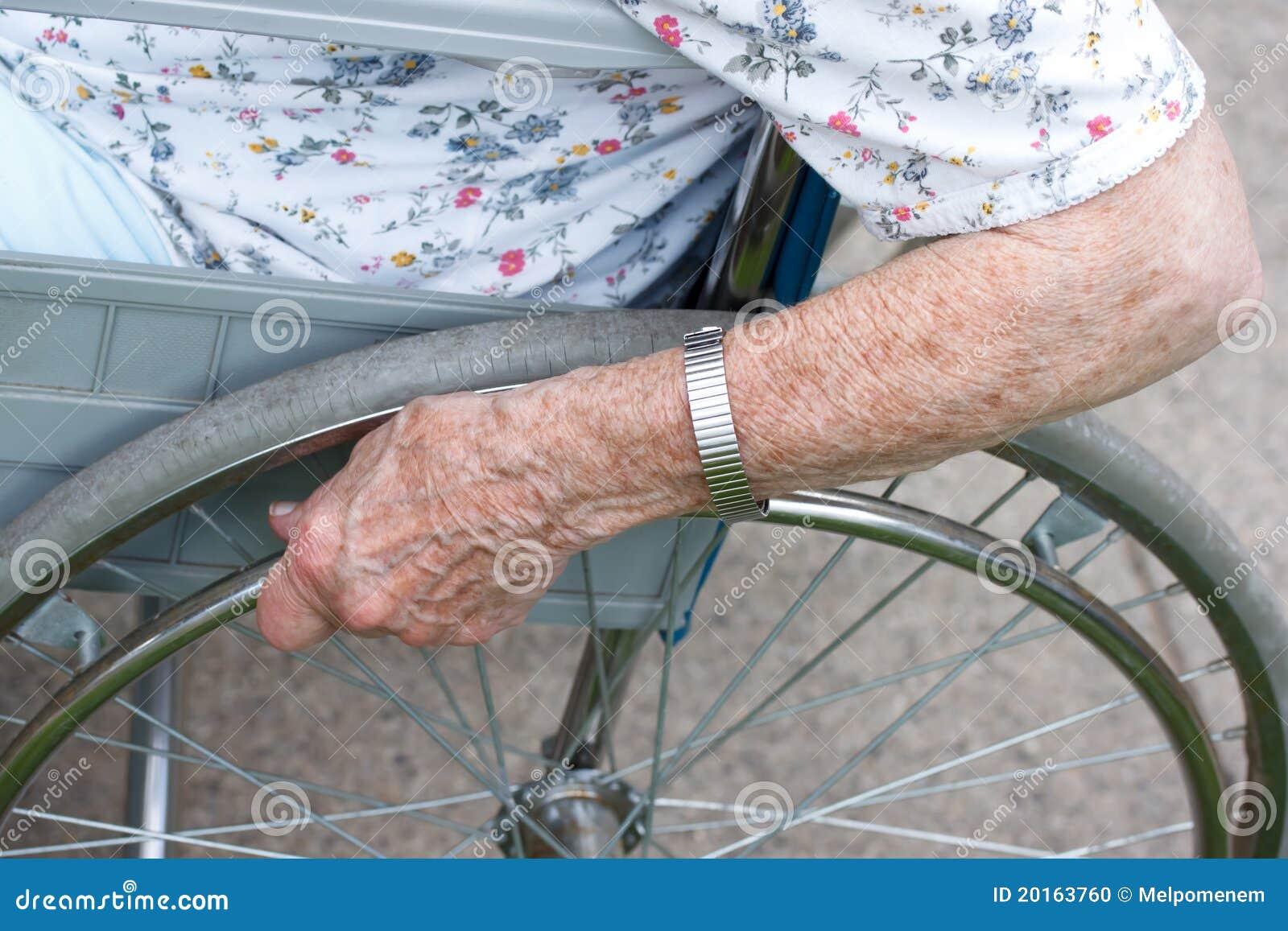 Mano dell 39 anziano sulla rotella della sedia a rotelle for Vecchio in sedia a rotelle
