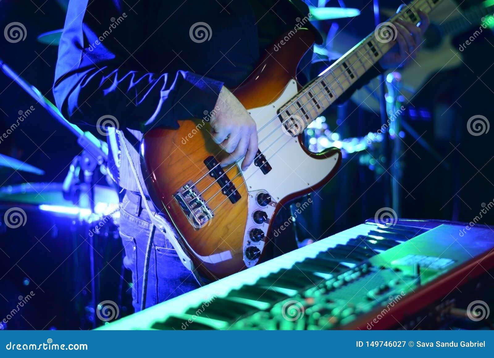 Mano dell uomo che gioca chitarra al concerto di musica durante la notte