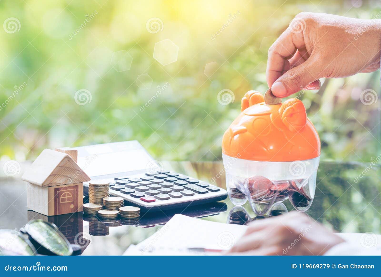 Mano dell uomo d affari che mette moneta in un porcellino salvadanaio Concetto per la scala della proprietà, l ipoteca e l invest
