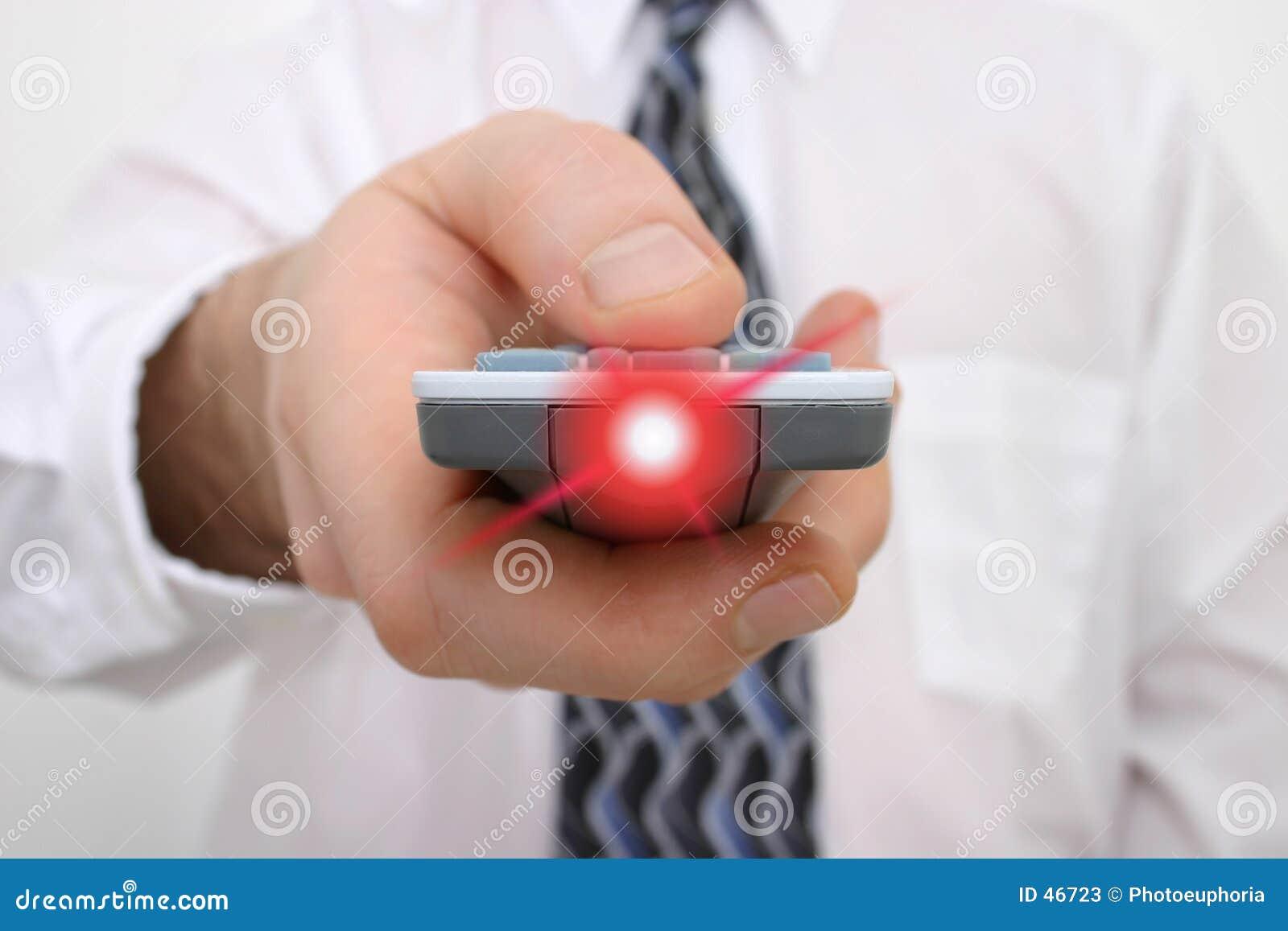 Mano dell uomo su un telecomando con indicatore luminoso che irradia dal periferico