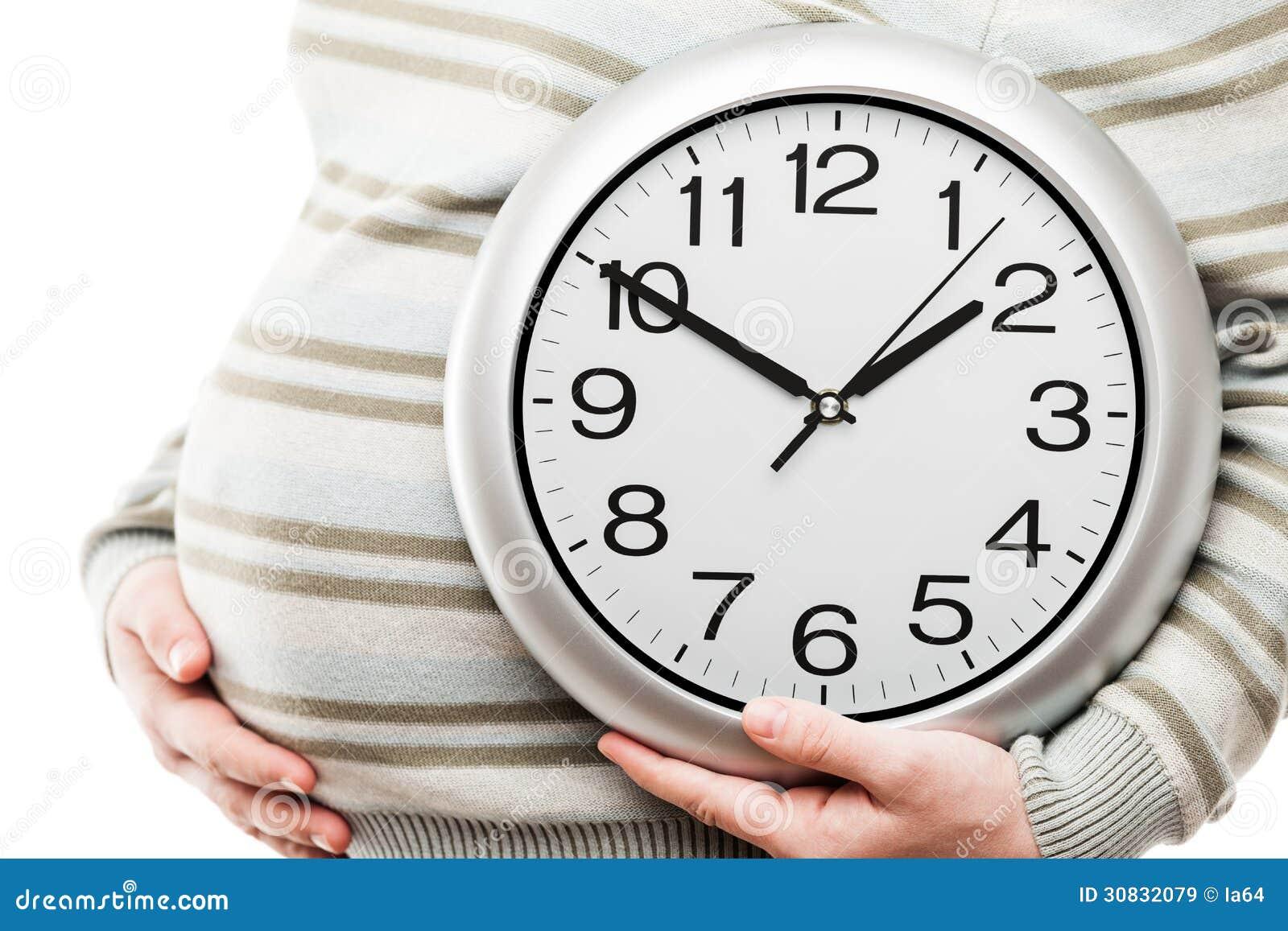 Mano della donna incinta che tiene il grande orologio di parete dell ufficio che mostra tempo