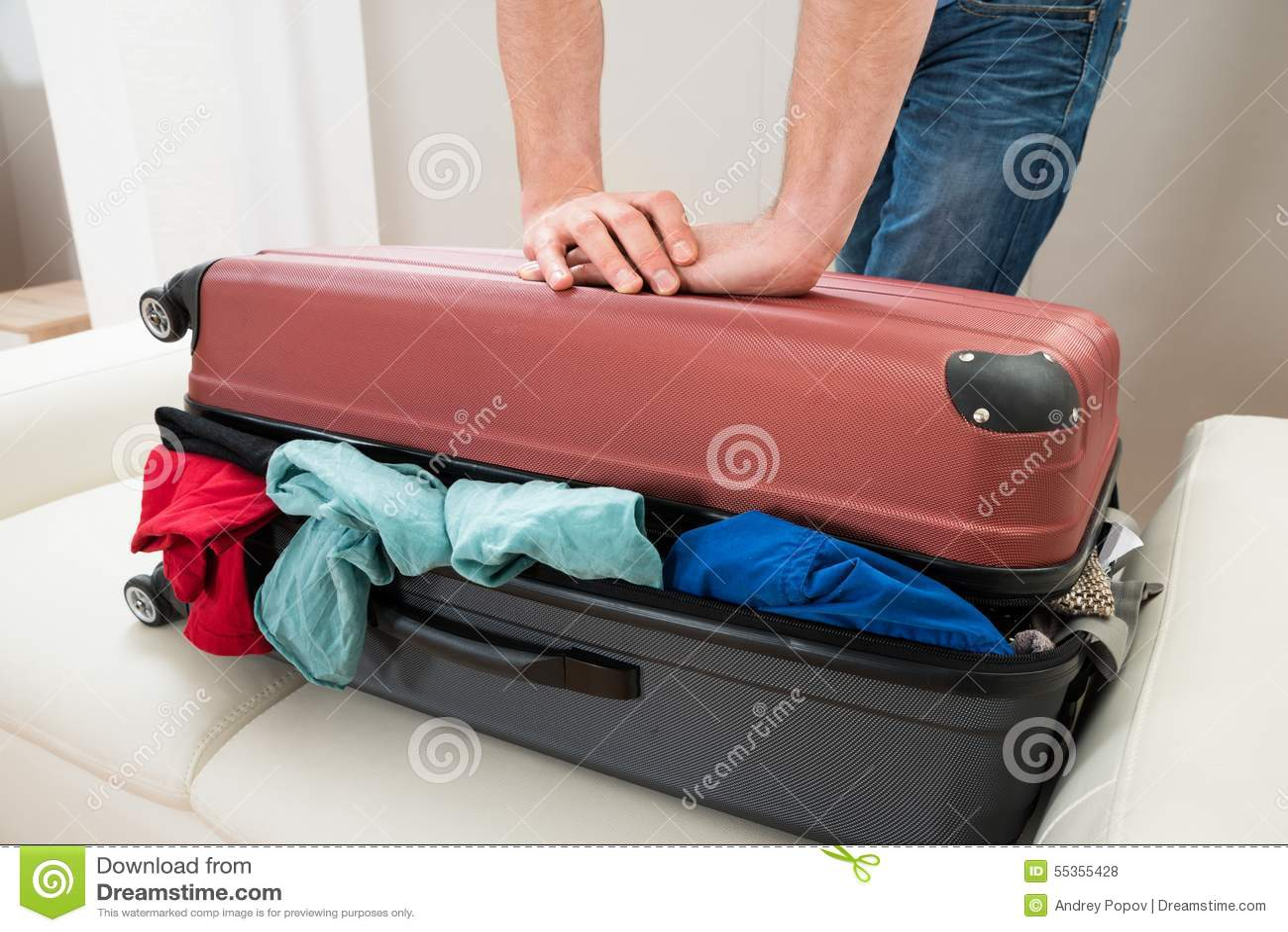 Mano della persona che prova a chiudere valigia