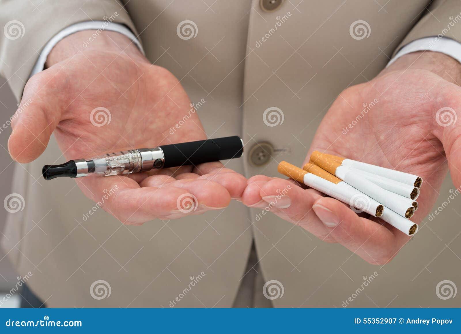 Mano della persona di affari con la sigaretta elettronica