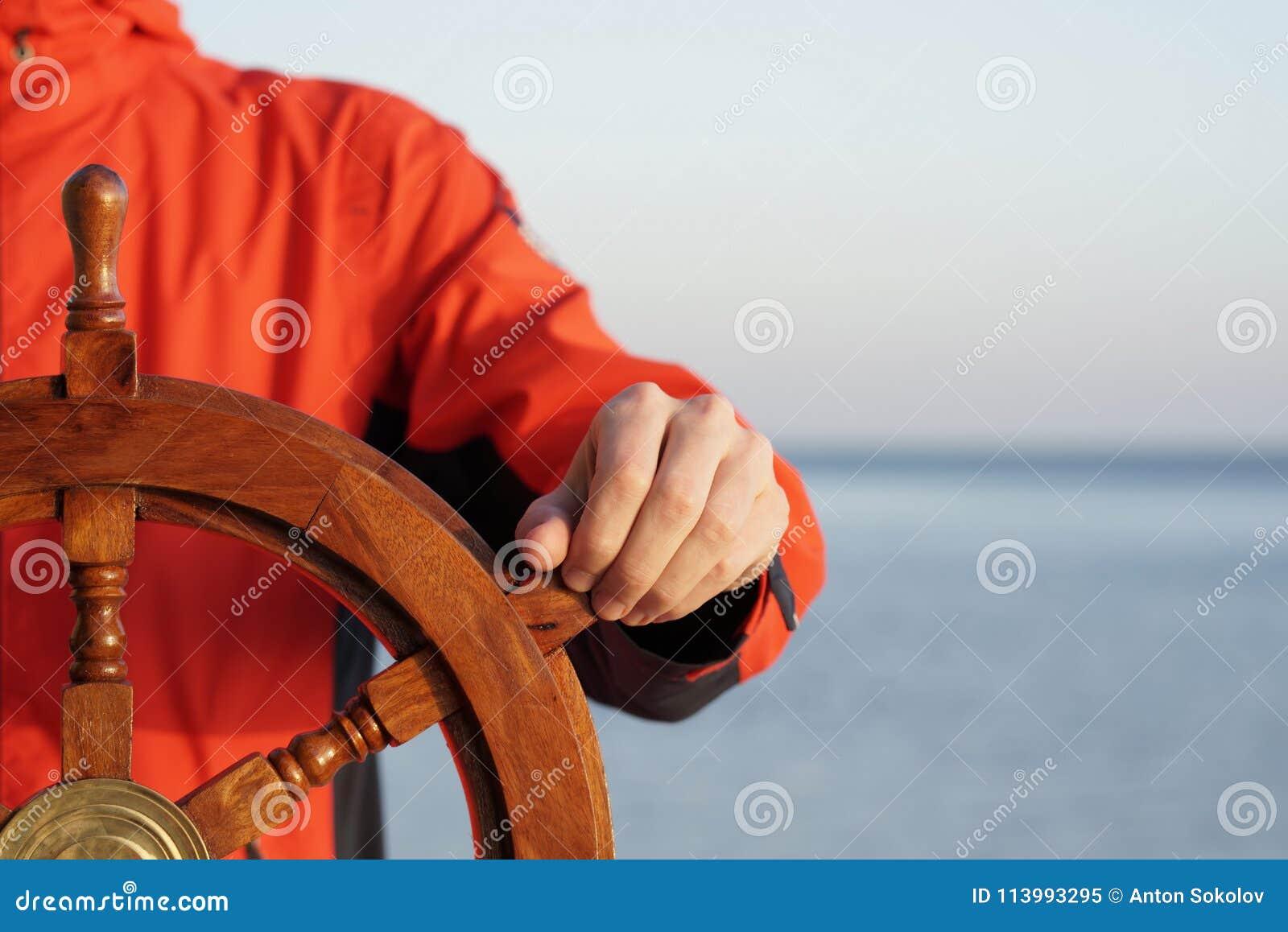 Mano della tenuta di capitano sul timone della nave