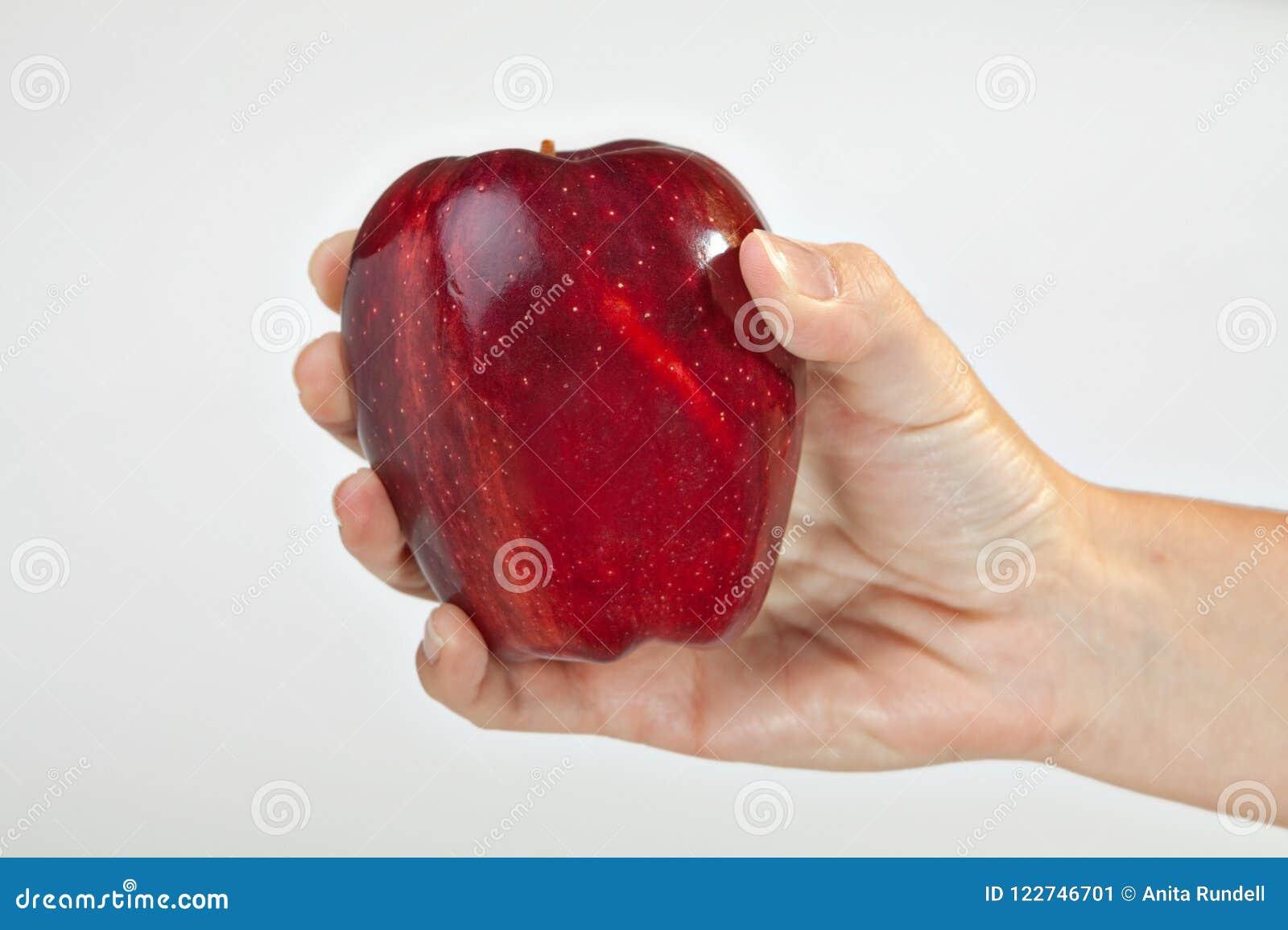 Mano derecha que sostiene Apple rojo