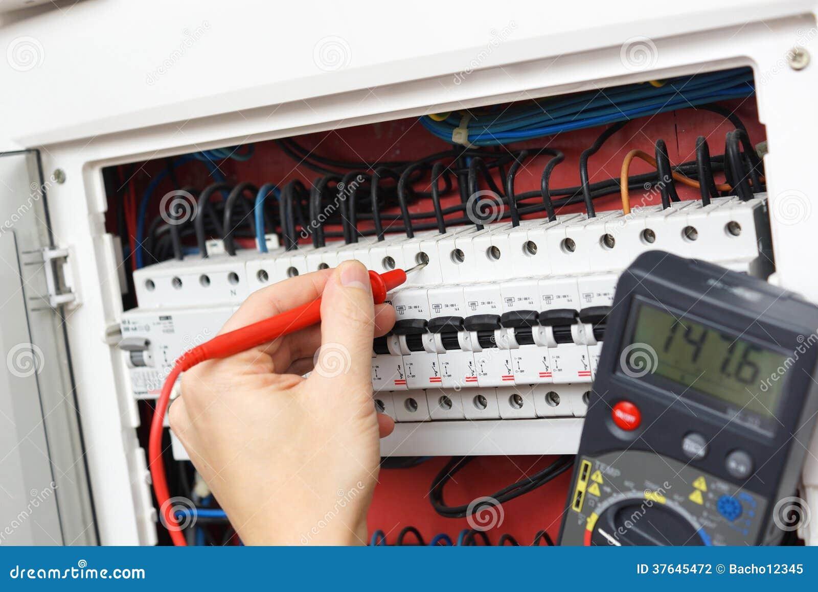 Mano di un elettricista con la sonda del multimetro ad un interruttore elettrico