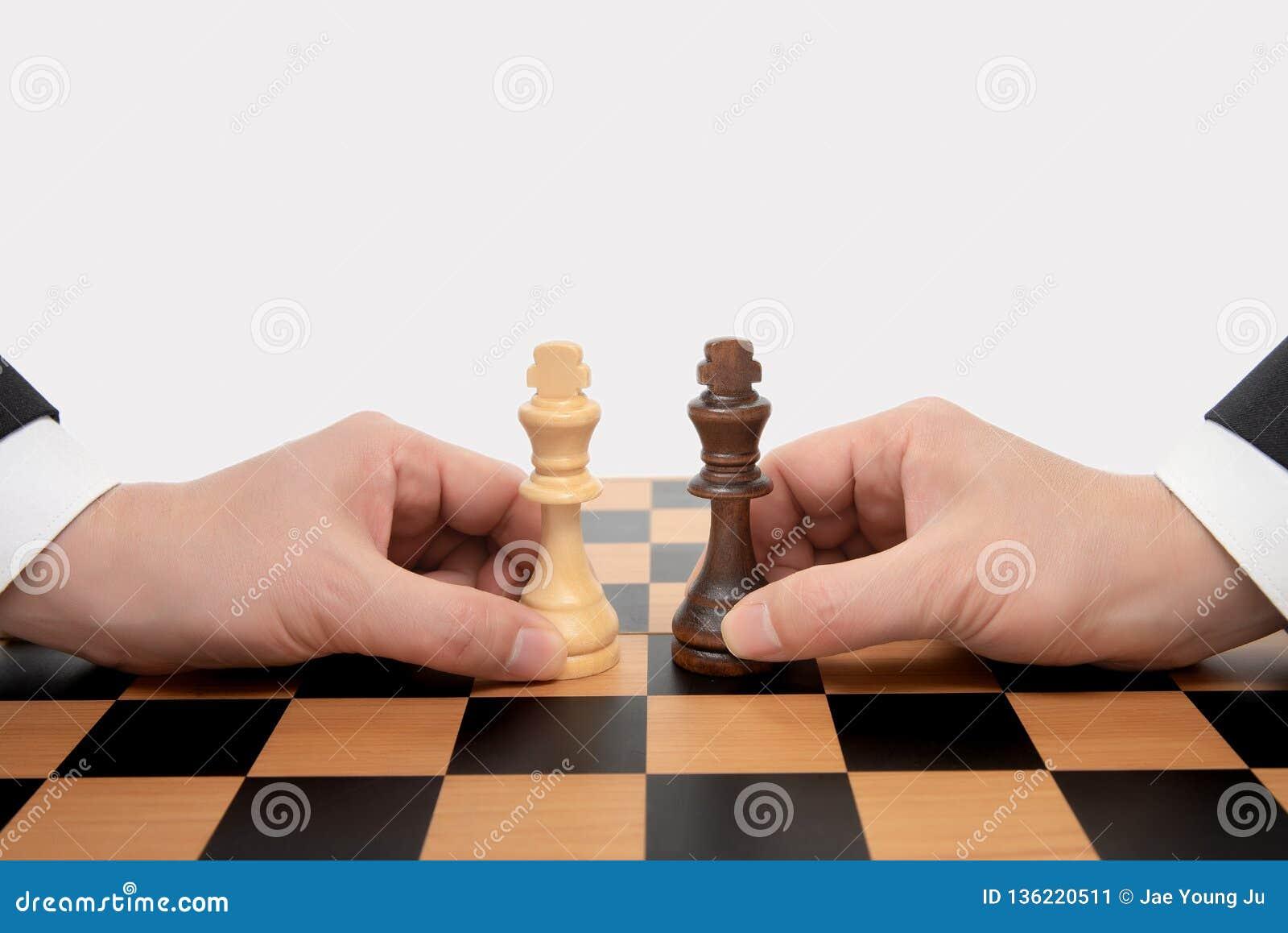 Mano di un uomo d affari commovente che tiene un pezzo degli scacchi di re Concetto di negoziato di affari