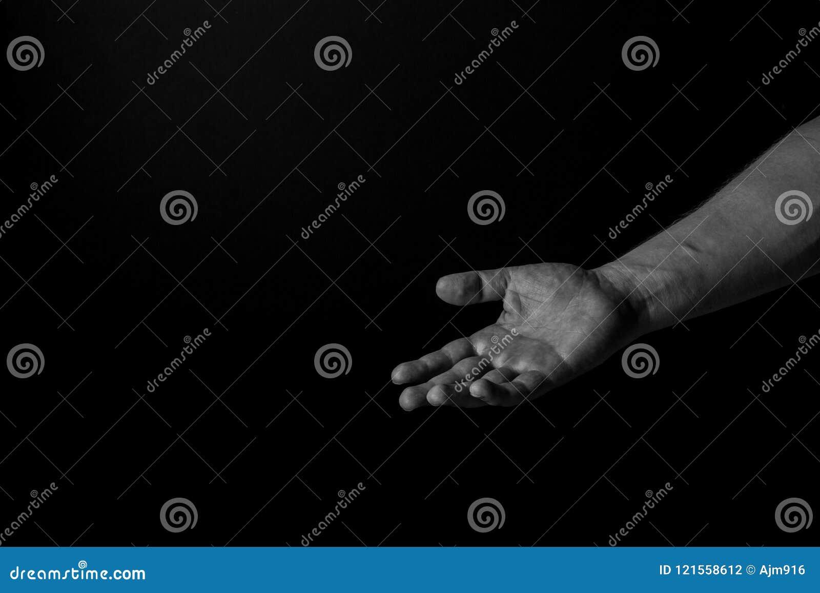 Mano di una palma dell uomo su che raggiunge, sul fondo nero, dante una mano amica Diami il vostro concetto della mano
