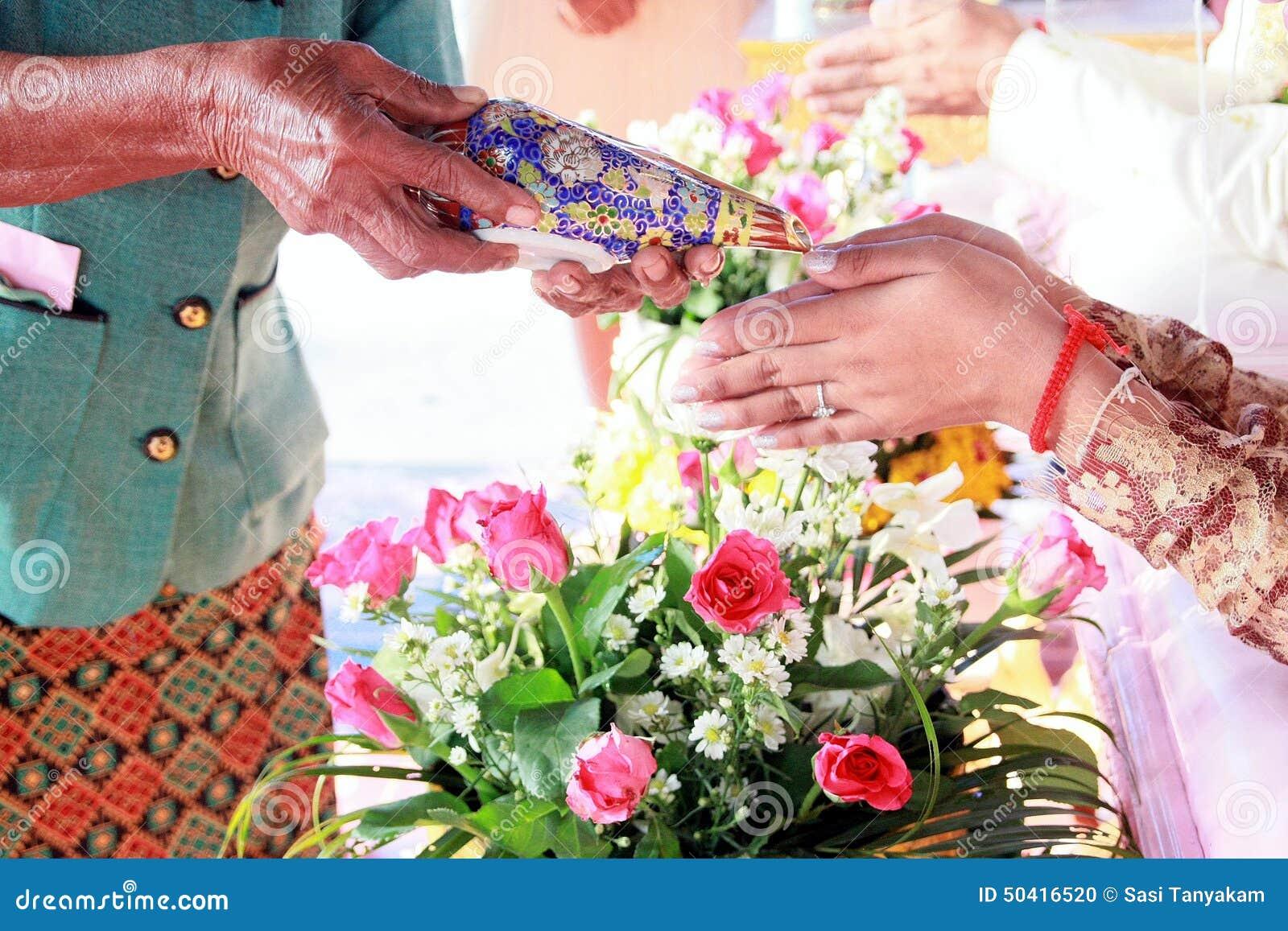e6630f2c4379 Mano di una sposa che riceve acqua santa dagli anziani nella cerimonia di  nozze tailandese della