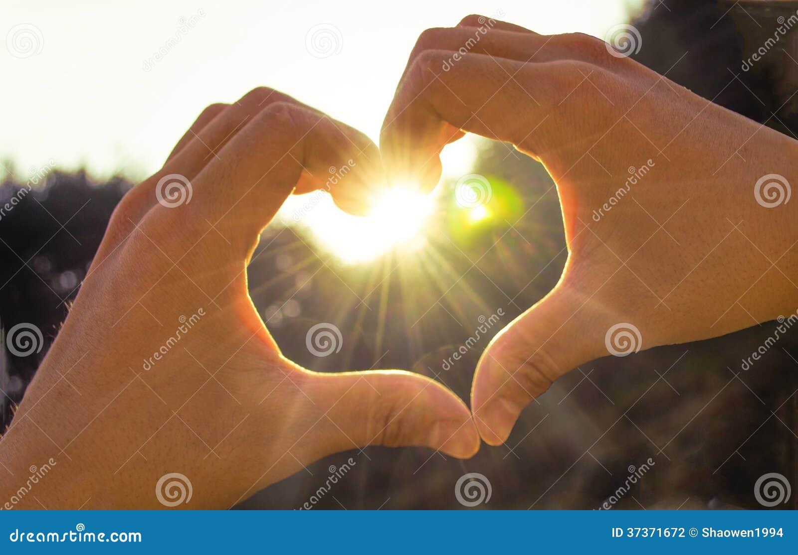 Mano en corazón de la sol del amor