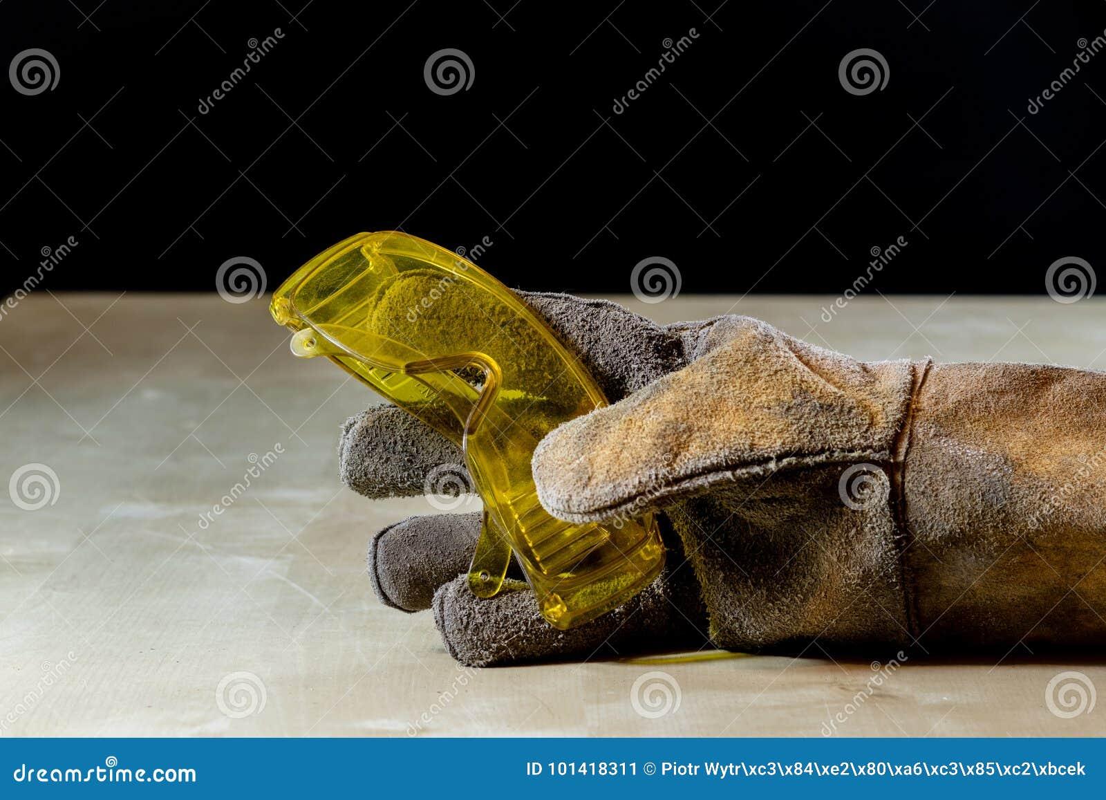 Mano en guante con la herramienta para el trabajo en taller Mano protegida cerca