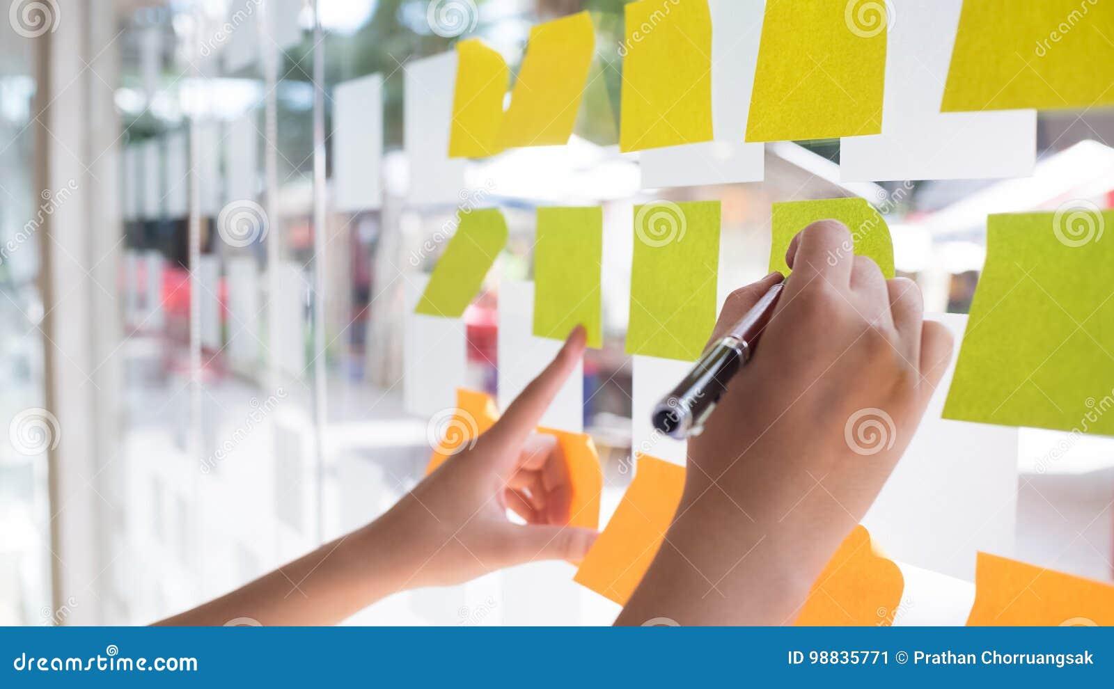 Mano facendo uso della nota appiccicosa di Post-it con  brainstorming  sulla carta per appunti