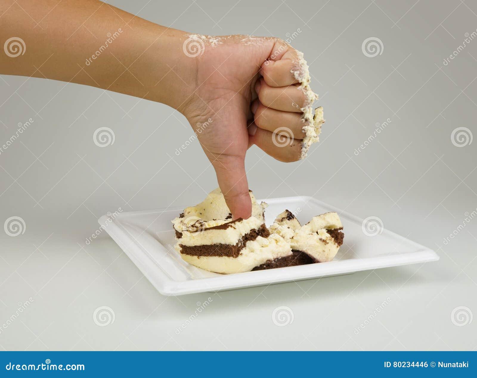 Mano femenina con un finger abajo Pulgares abajo en el fondo de la torta Torta no sabrosa Torta de la aversión El concepto es des