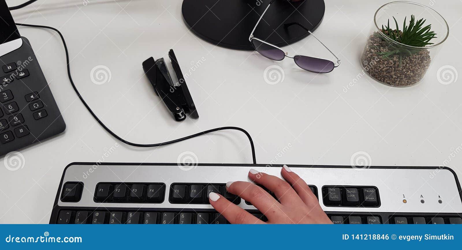 Mano femenina en el teclado de ordenador negro cerca de los vidrios de la grapadora del teléfono de la oficina