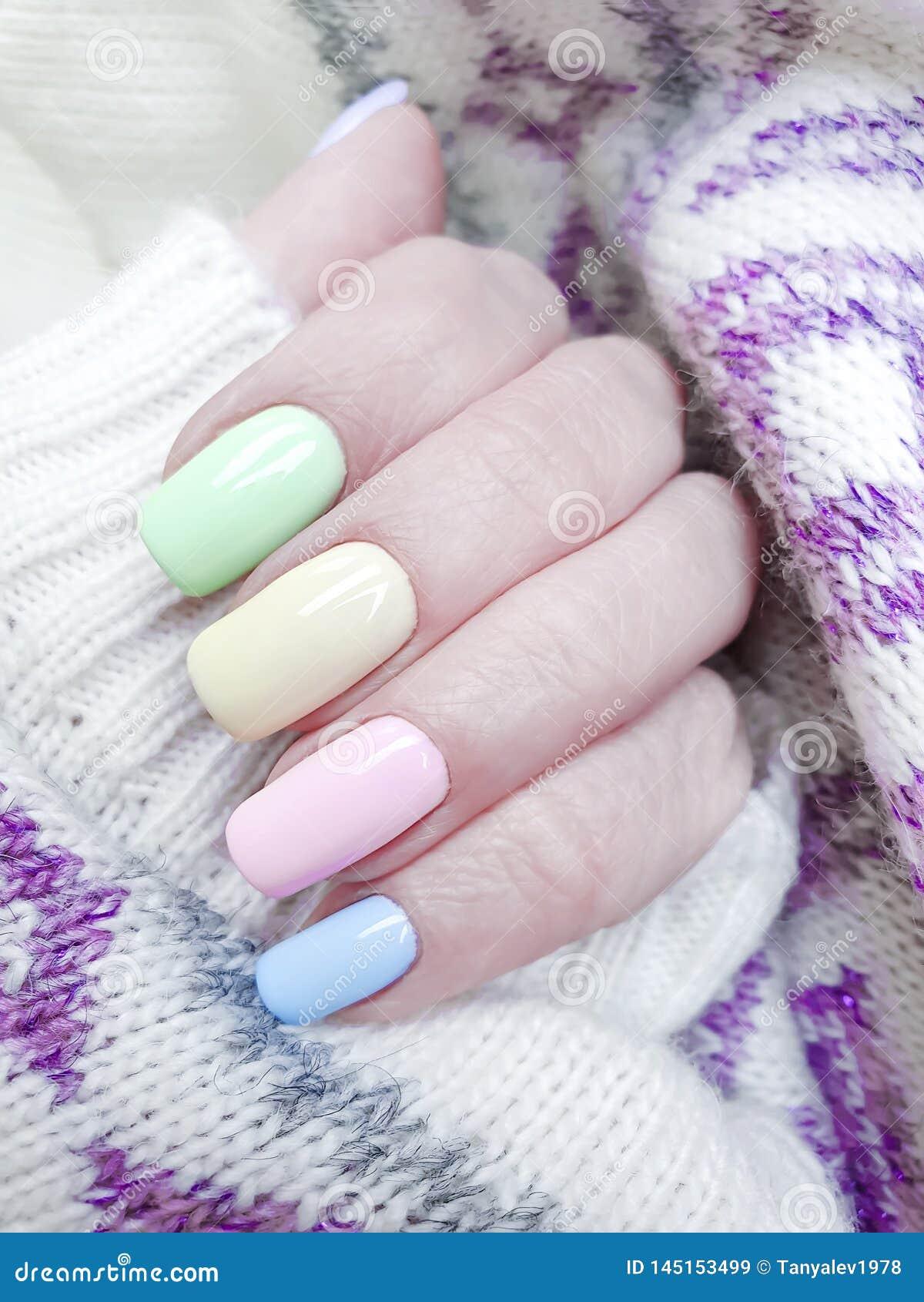 Mano femenina, invierno hermoso de la moda del suéter de la decoración del diseño de la manicura