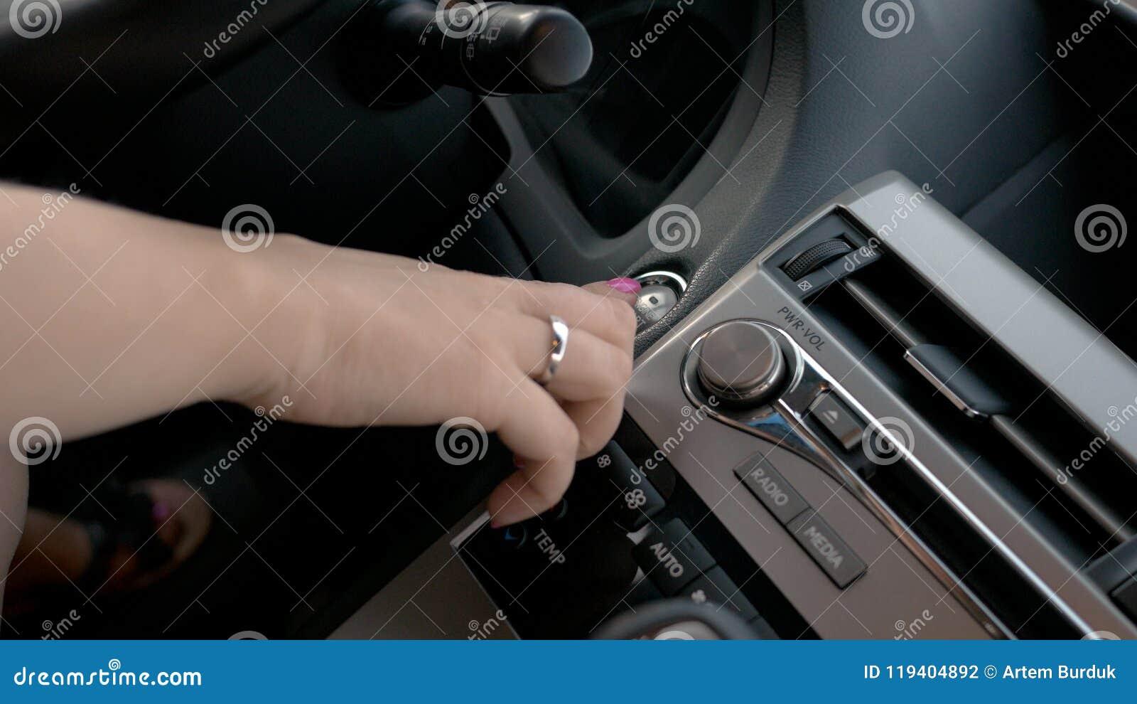 Mano femminile che avvia il motore dell automobile, donna di affari che conduce veicolo di lusso, fine su