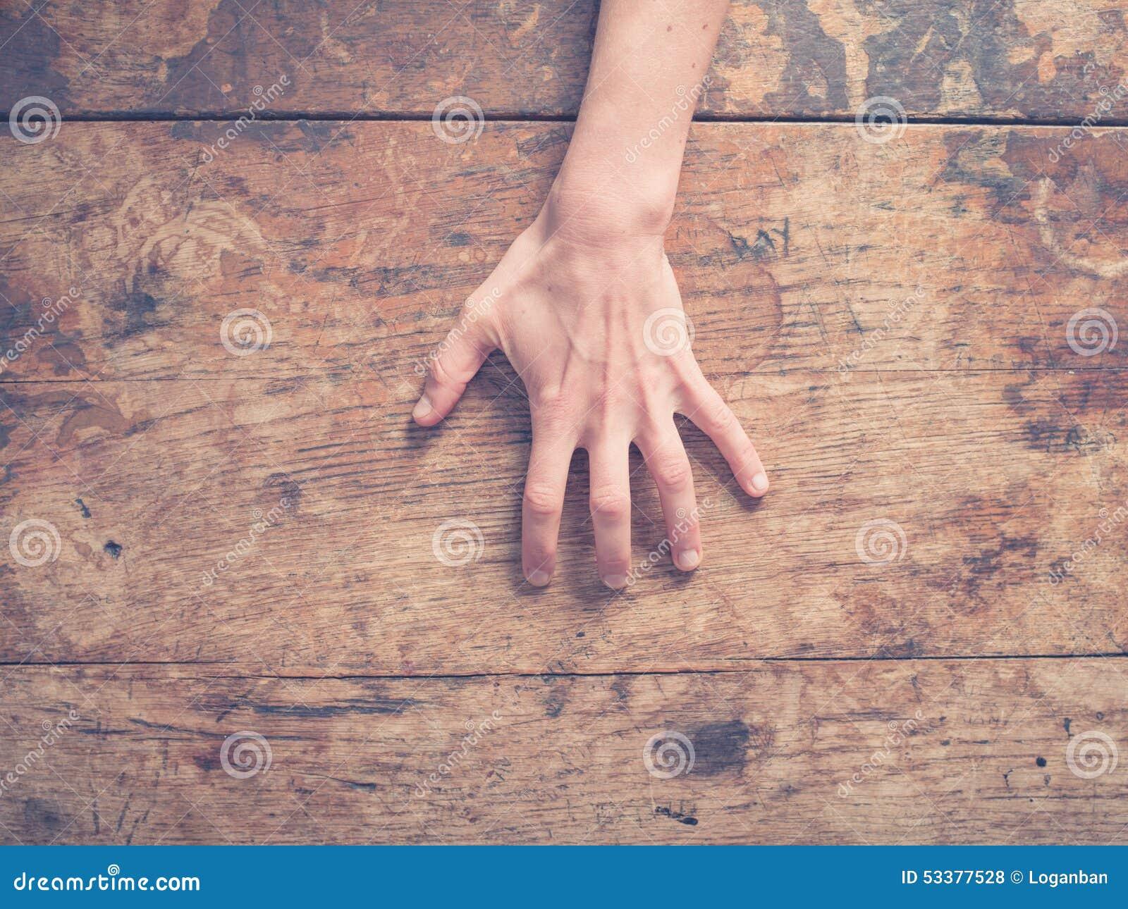 Mano femminile che graffia tavola di legno