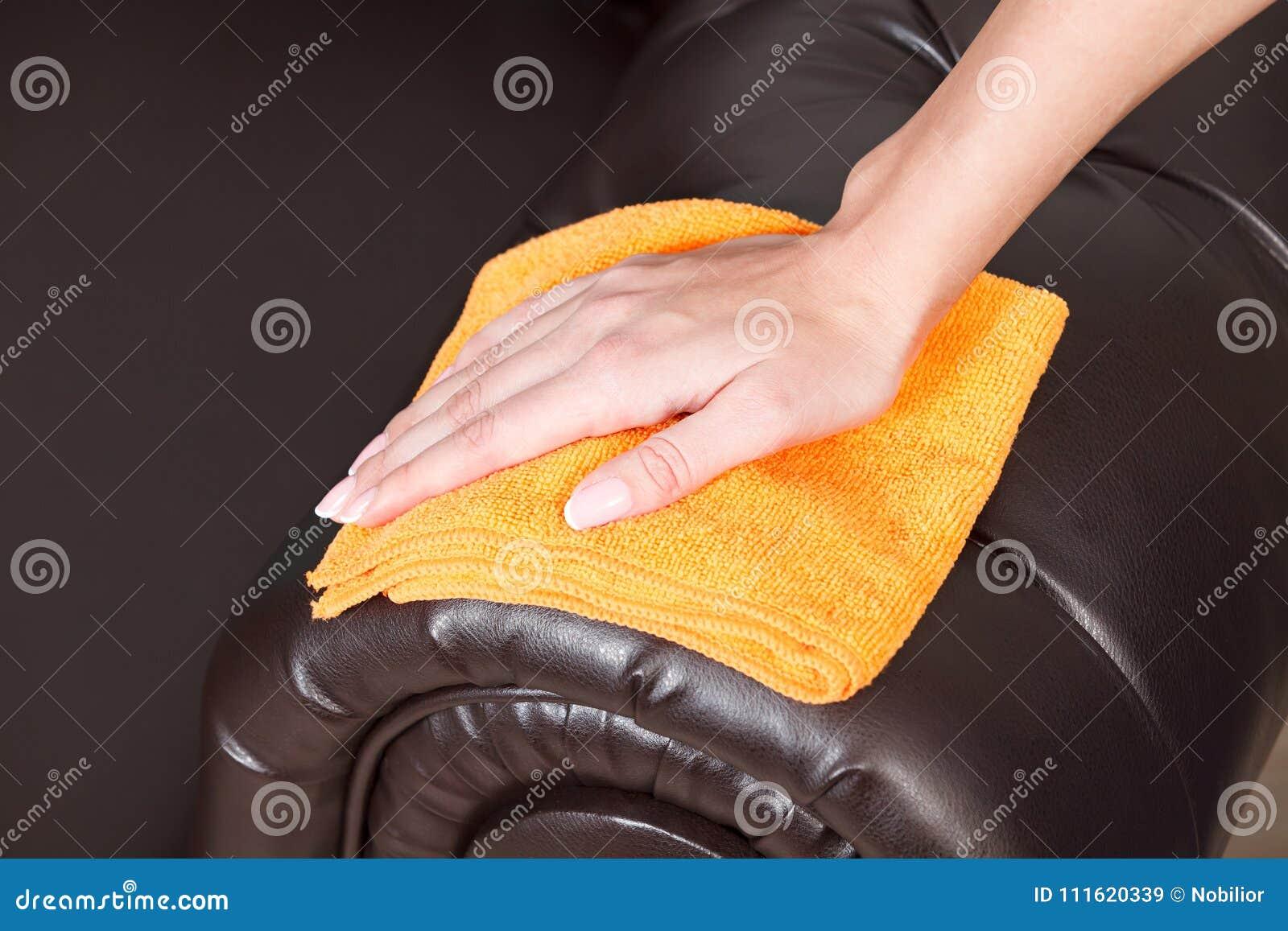 Mano femminile che pulisce lo strato o il sofà di cuoio marrone di Chester