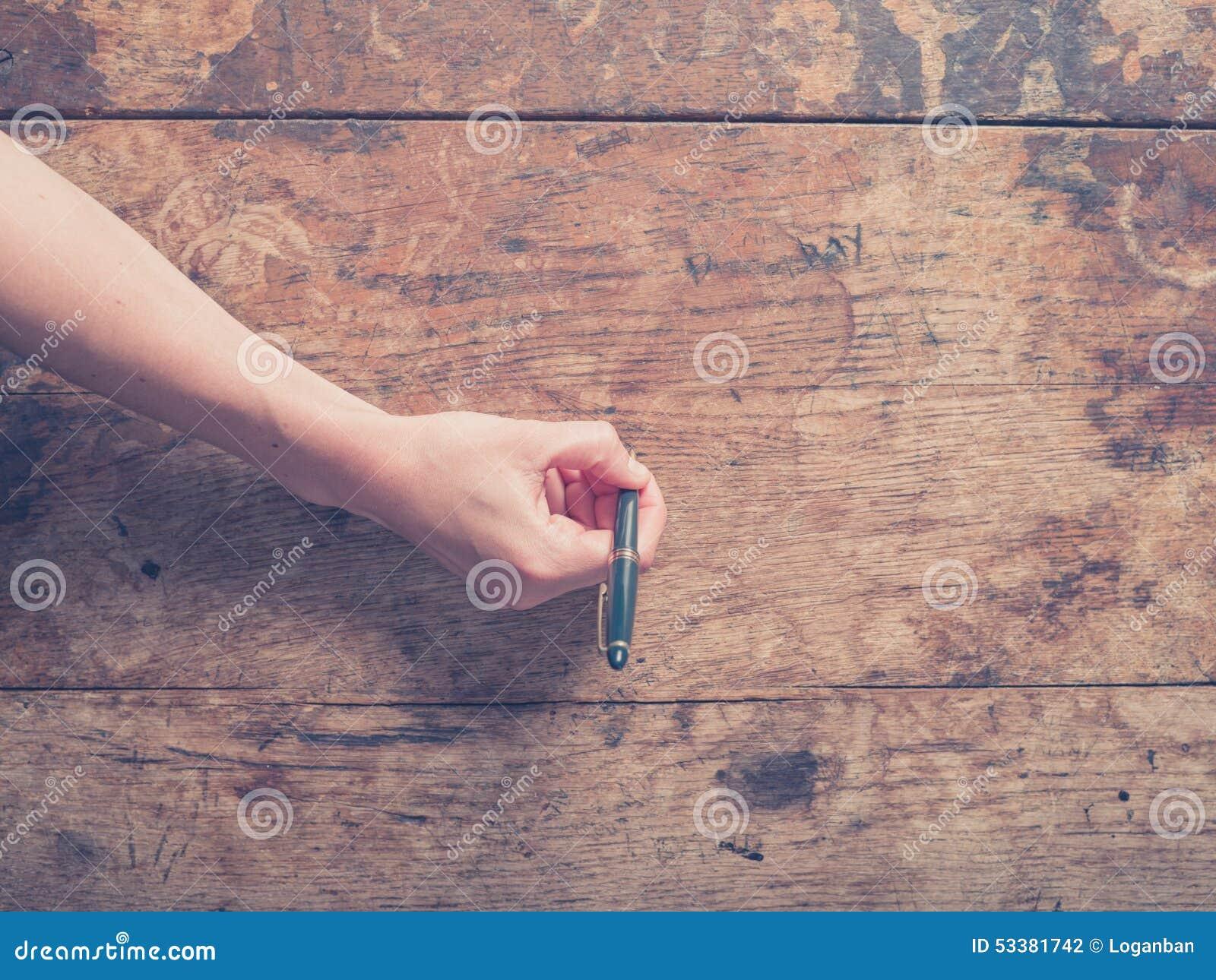 Mano femminile che riting sullo scrittorio