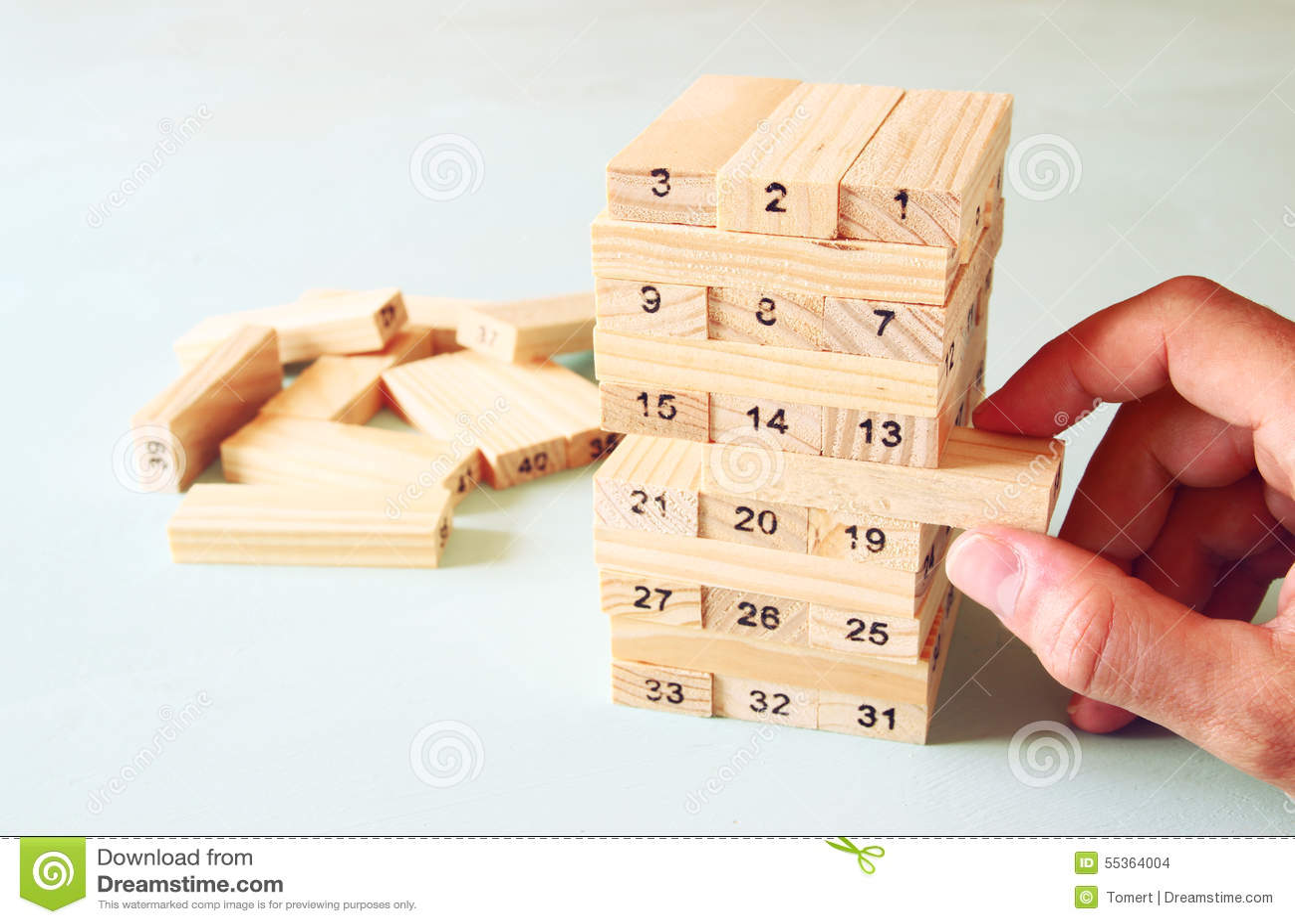 Mano maschio che dispone blocco di legno su una torre concetto di strategia e di piallatura