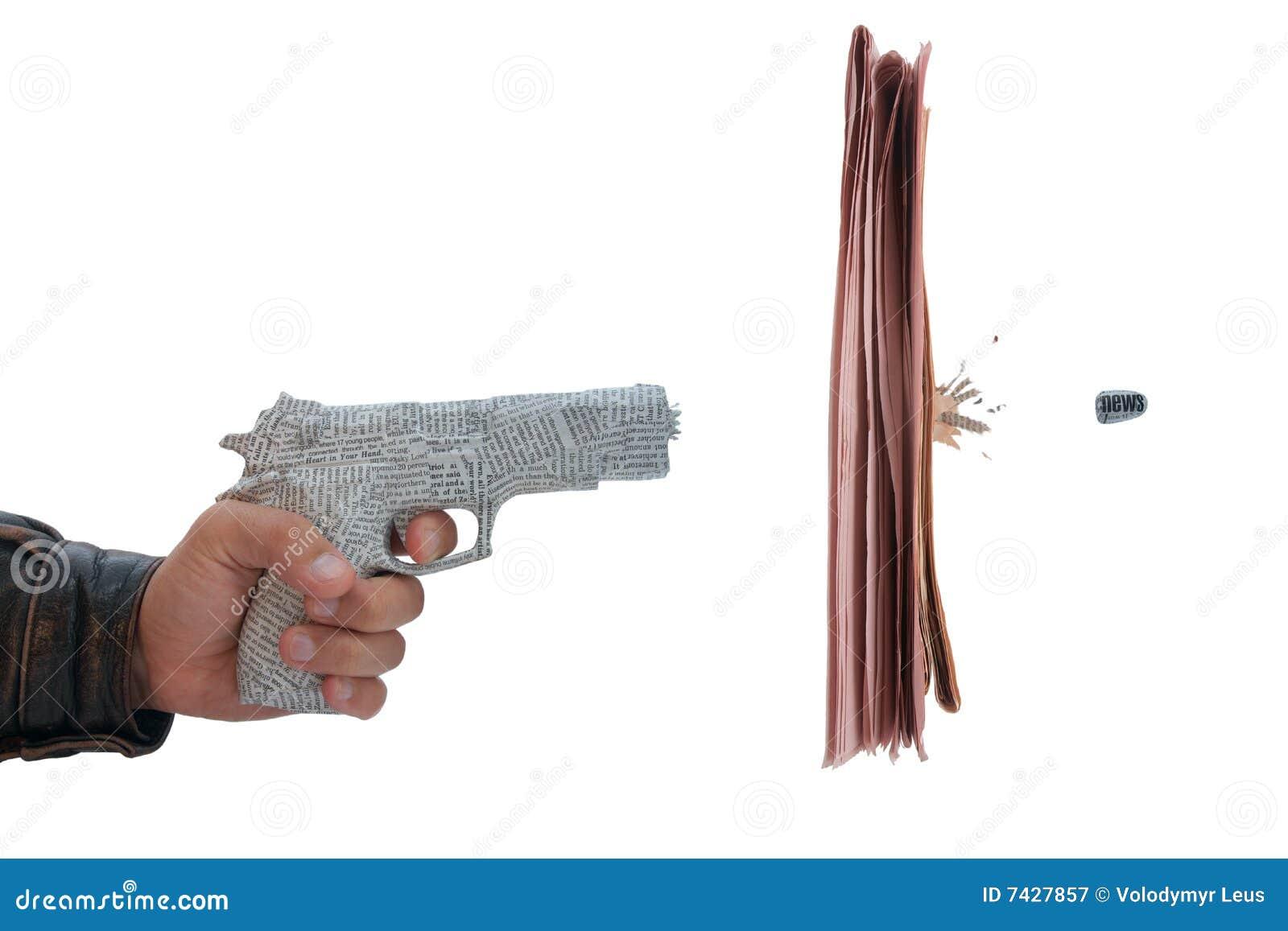 Mano masculina con el fuego una pistola del periódico del tiro