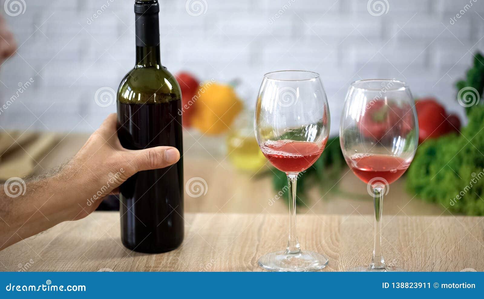 Mano masculina que sostiene la botella de vino, cristales en la tabla, degustation del alcohol