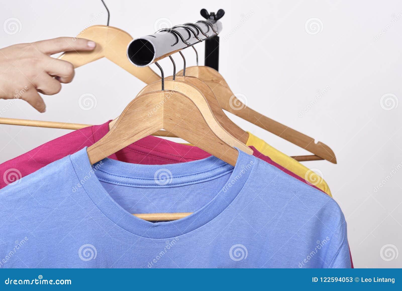 997866d123 Mano masculina que toma una suspensión para la ropa del estante aislado  sobre el fondo blanco