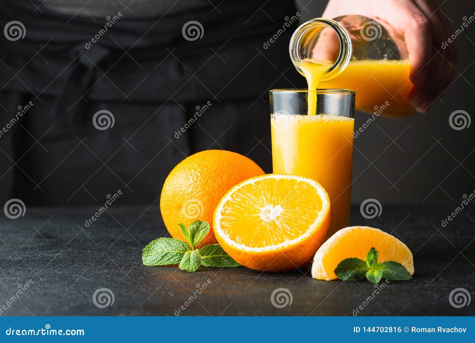 Mano masculina que vierte el zumo de naranja en un vidrio