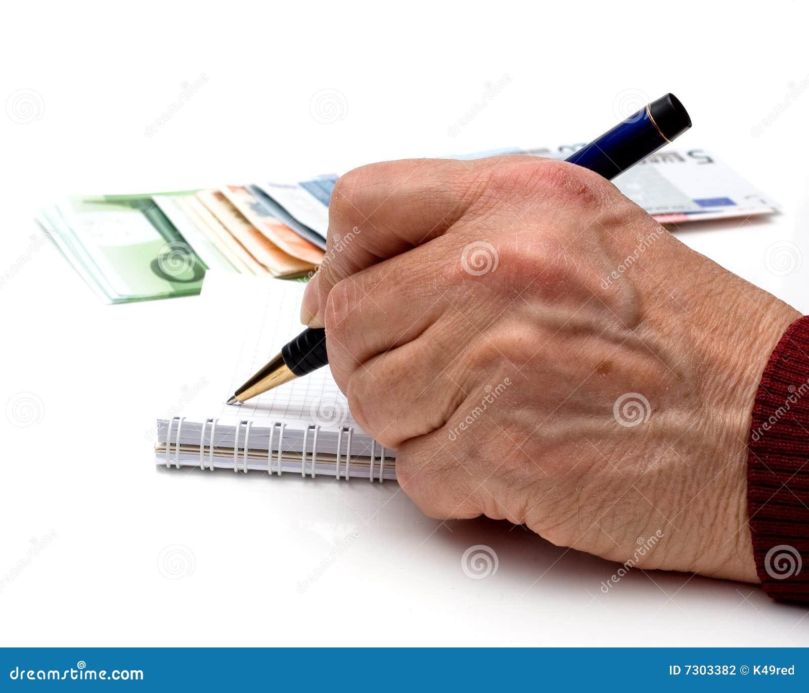 Mano, penna, taccuino e soldi