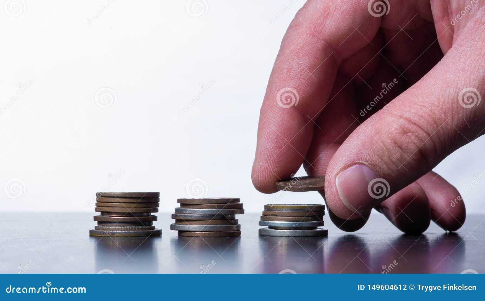 Mano que apila pequeñas monedas en una tabla