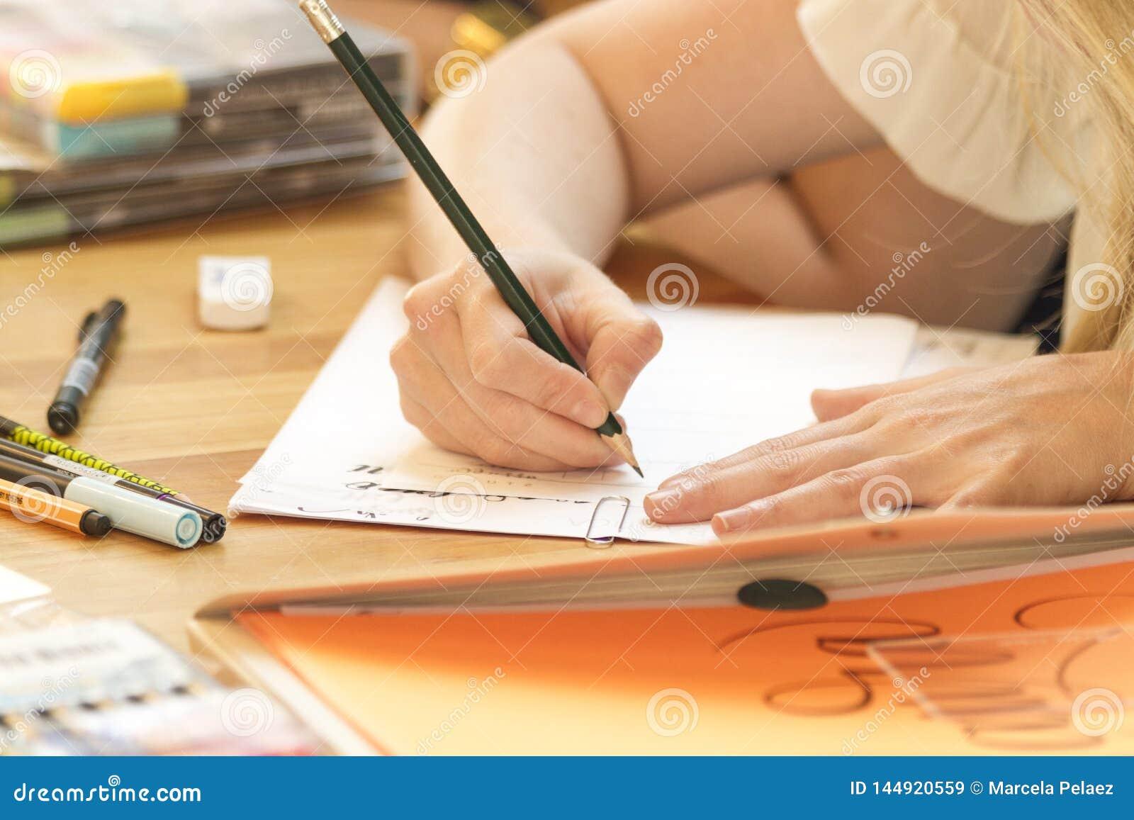 Mano que aprende las letras en clase con el l?piz negro y Libro Blanco y caos en escritorio