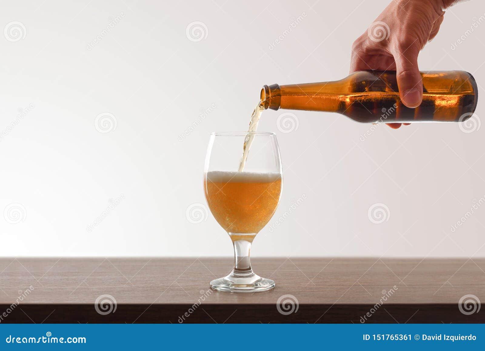 Mano que celebra embotellado de la cerveza un fondo blanco de la taza de cristal