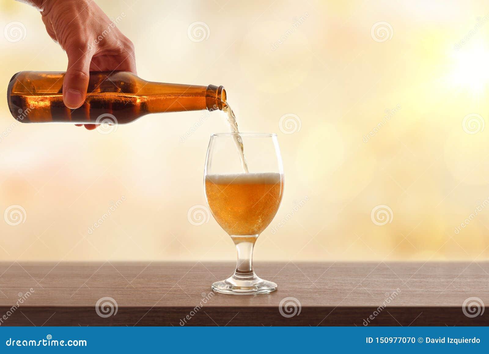 Mano que celebra embotellado de la cerveza un fondo de oro de la taza de cristal