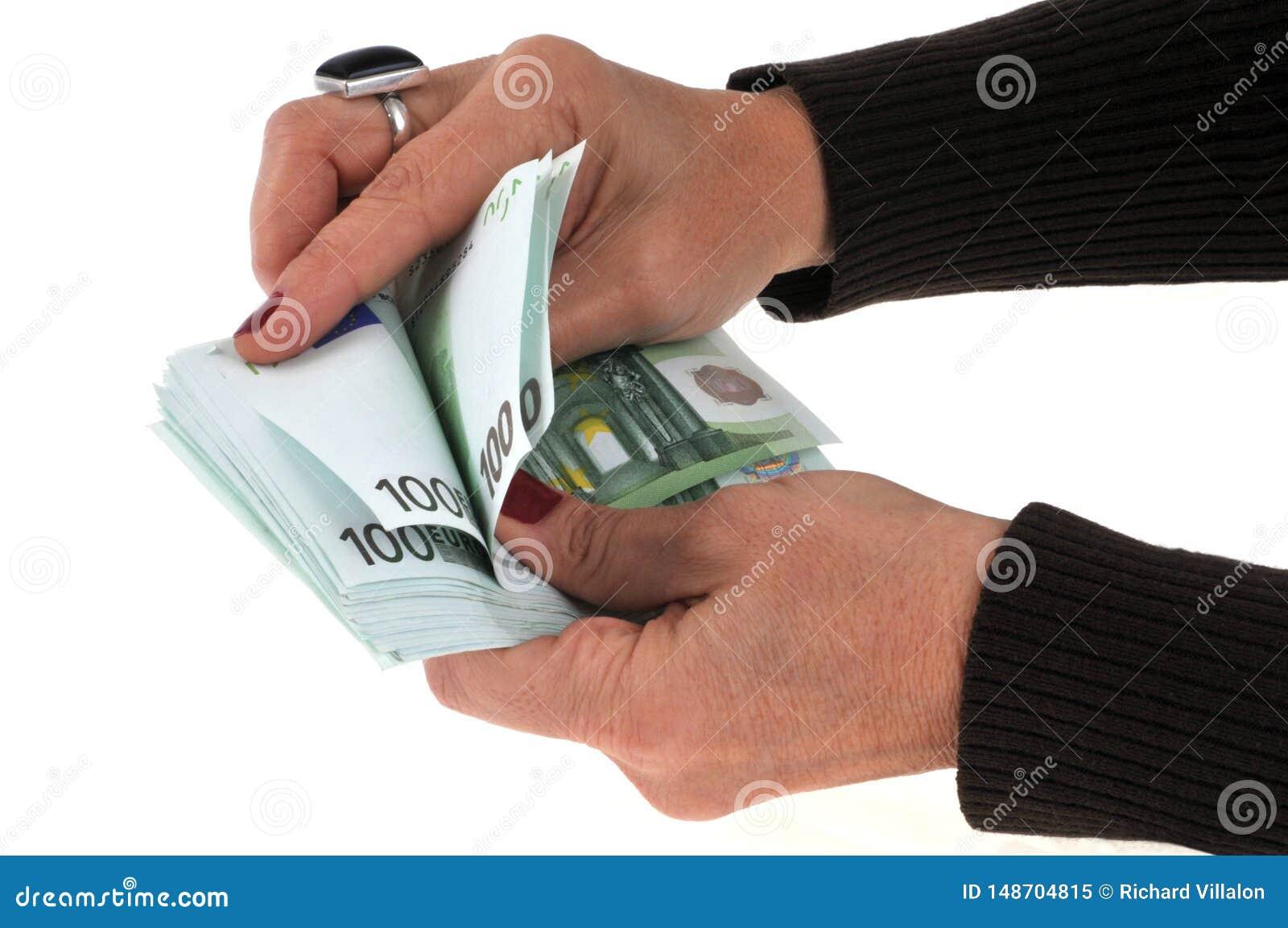 Mano que cuenta un taco de las cuentas de cientos euros