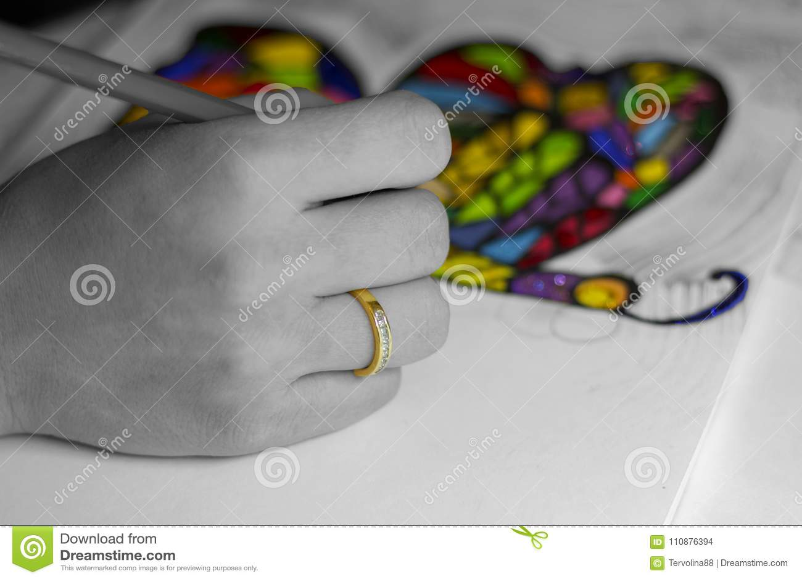 Mano que dibuja una mariposa colorida del arco iris