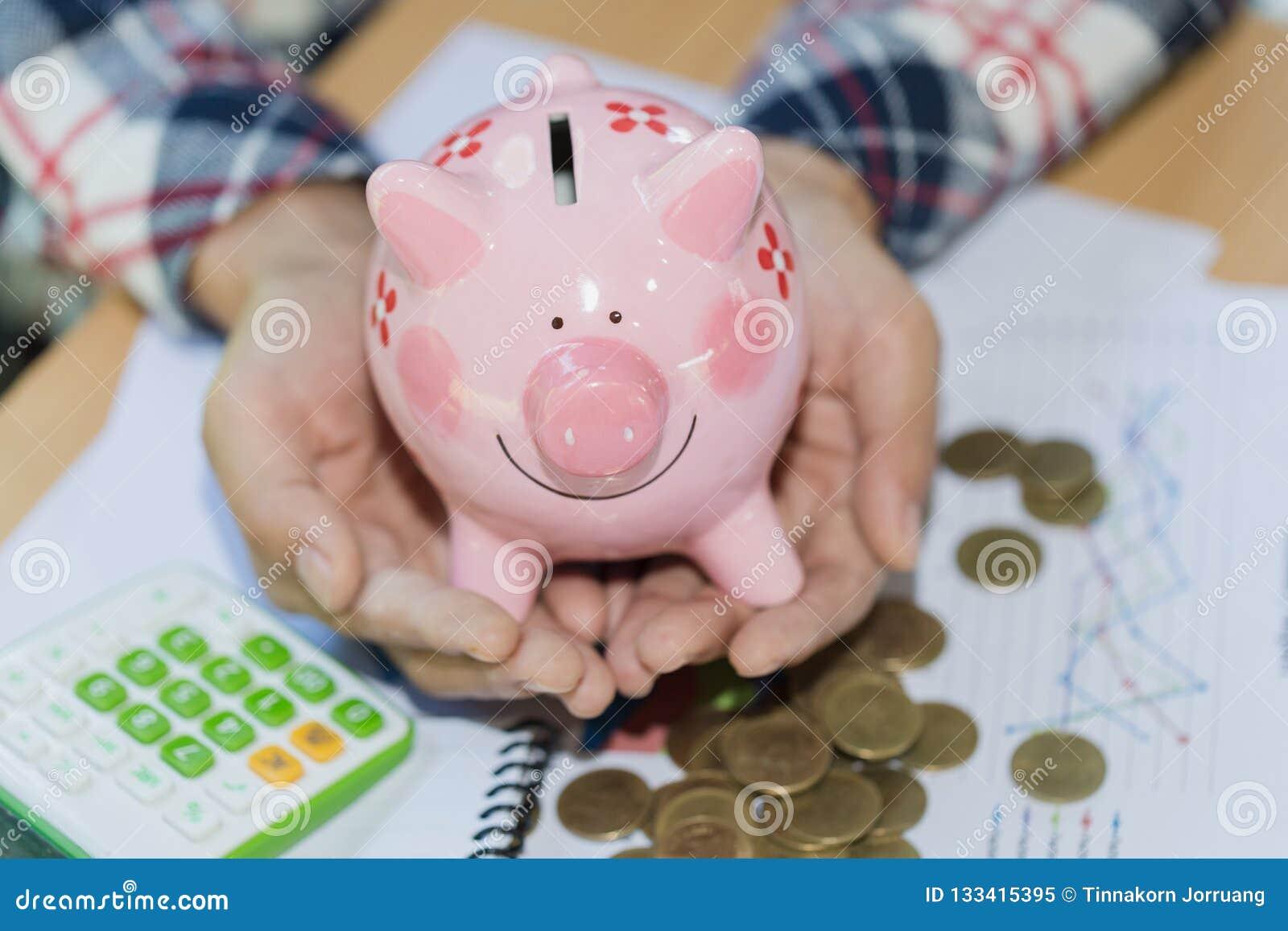 Mano que lleva a cabo la hucha rosada, el dinero de la reserva y el investm financiero